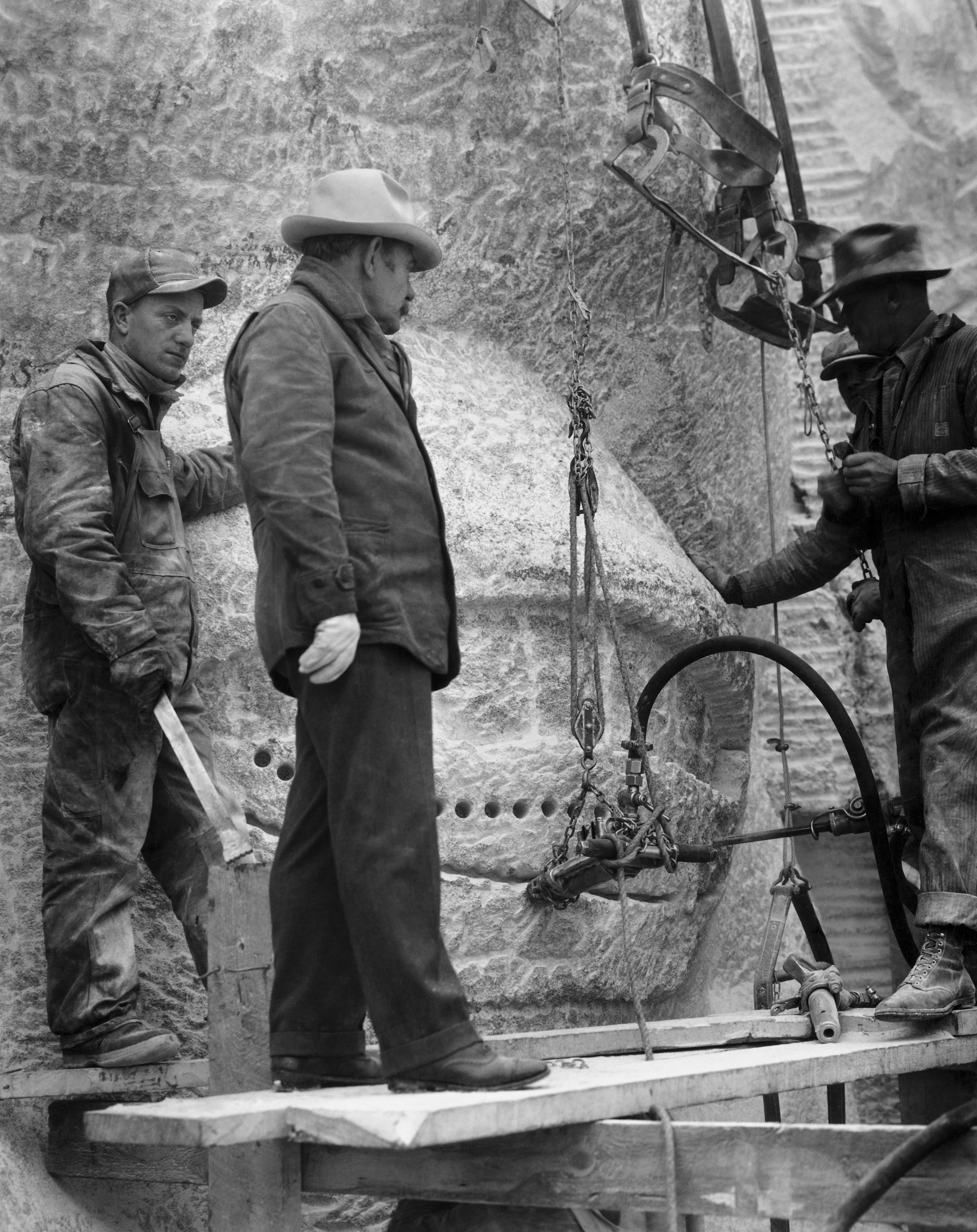 American sculptor Gutzon Borglum (c), who is leading the Mount Rushmore National Memorial project, talks with a group of sculptors while inspecting an eye of one of the presidential heads in the Black Hills area of Keystone, S.D., circa 1930s.