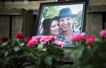 A portrait of Neeltje Tol and Cor Schilder is placed with flowers and candles in front of their flower shop in Volendam, Netherlands,July 19, 2014.