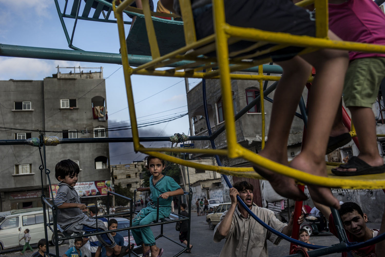 Jul. 29, 2014. Smoke billows in the background from the site of an Israeli strike as Palestinian children play on a mini ferris wheel in the northern Gaza Strip town of Beit Lahiya.