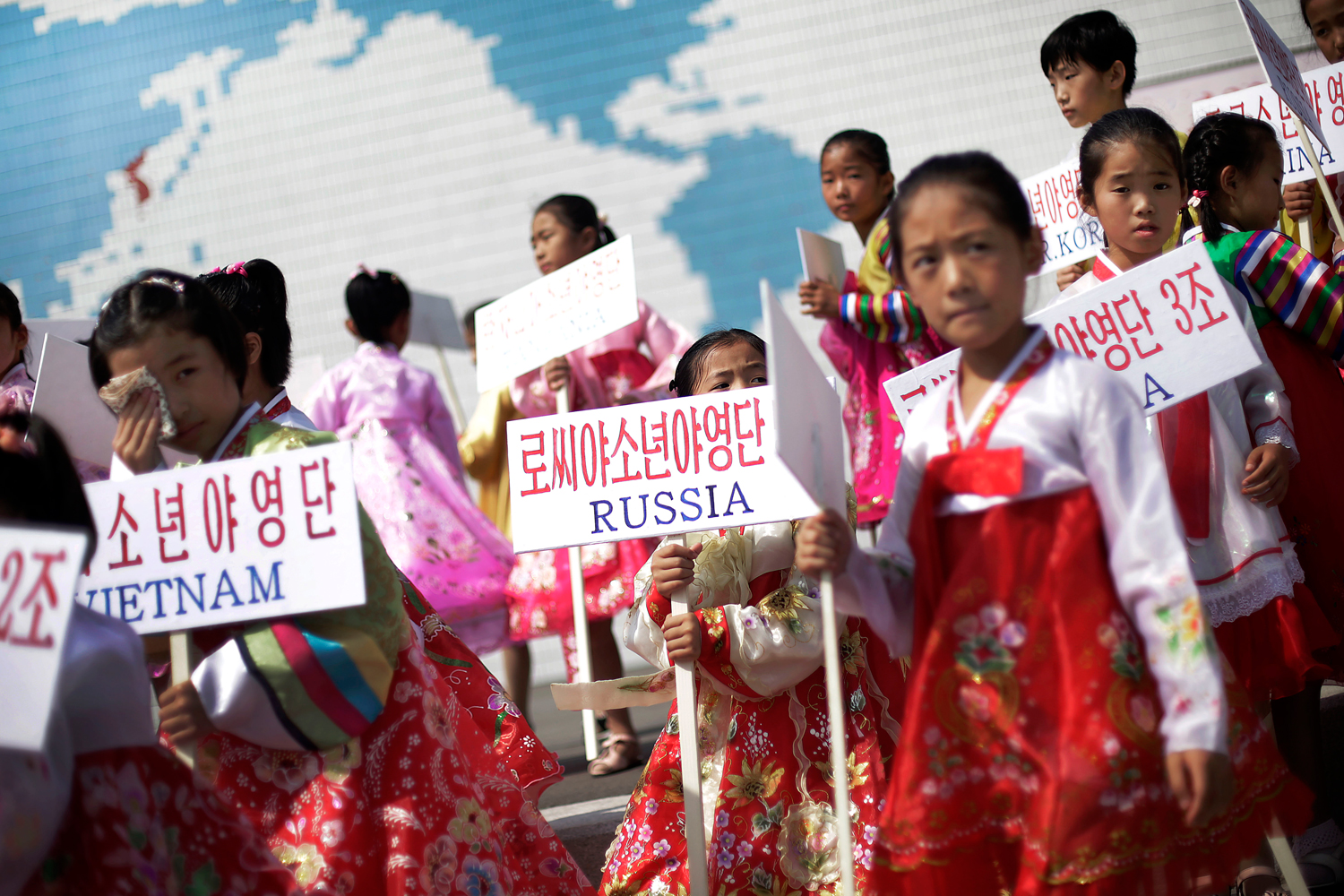 Young North Korean girls hold up signboards with the names of participating countries during an opening ceremony at the Songdowon International Children's Camp, Tuesday, July 29, 2014, in Wonsan, North Korea.