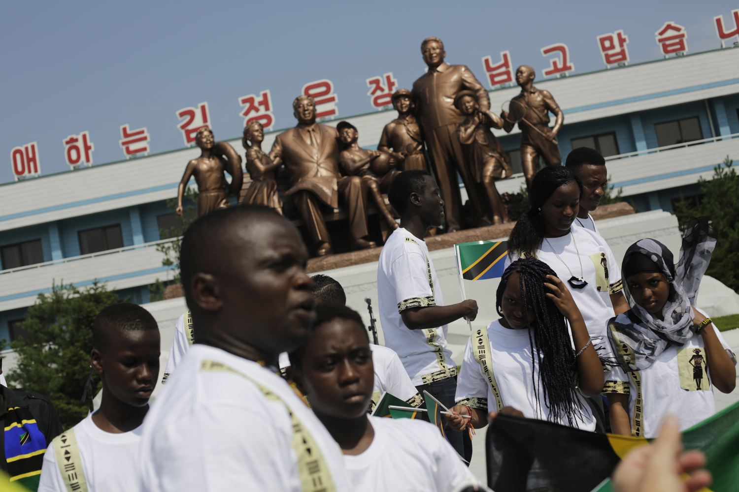 Students from the Laureat International School in Tanzania walk past a statue of the late North Korean leaders Kim Il Sung and Kim Jong Il, surrounded by children, on the parade square of the Songdowon International Children's Camp, Tuesday, July 29, 2014, in Wonsan, North Korea.