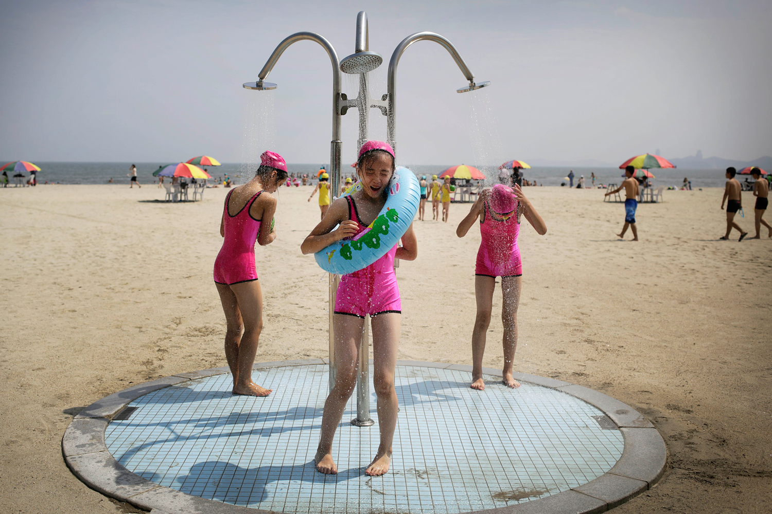 North Korean girls in similar bathing suits stand under a shower at the Songdowon International Children's Camp, Tuesday, July 29, 2014, in Wonsan, North Korea.