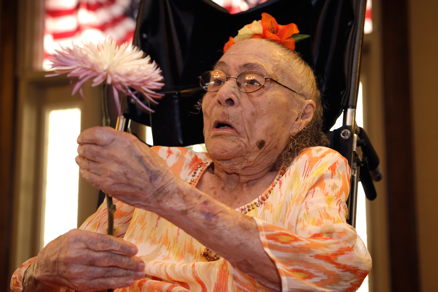 Gertrude Weaver holds a flower given to her a day before her 116th birthday at Silver Oaks Health and Rehabilitation in Camden, Ark on July 3, 2014.