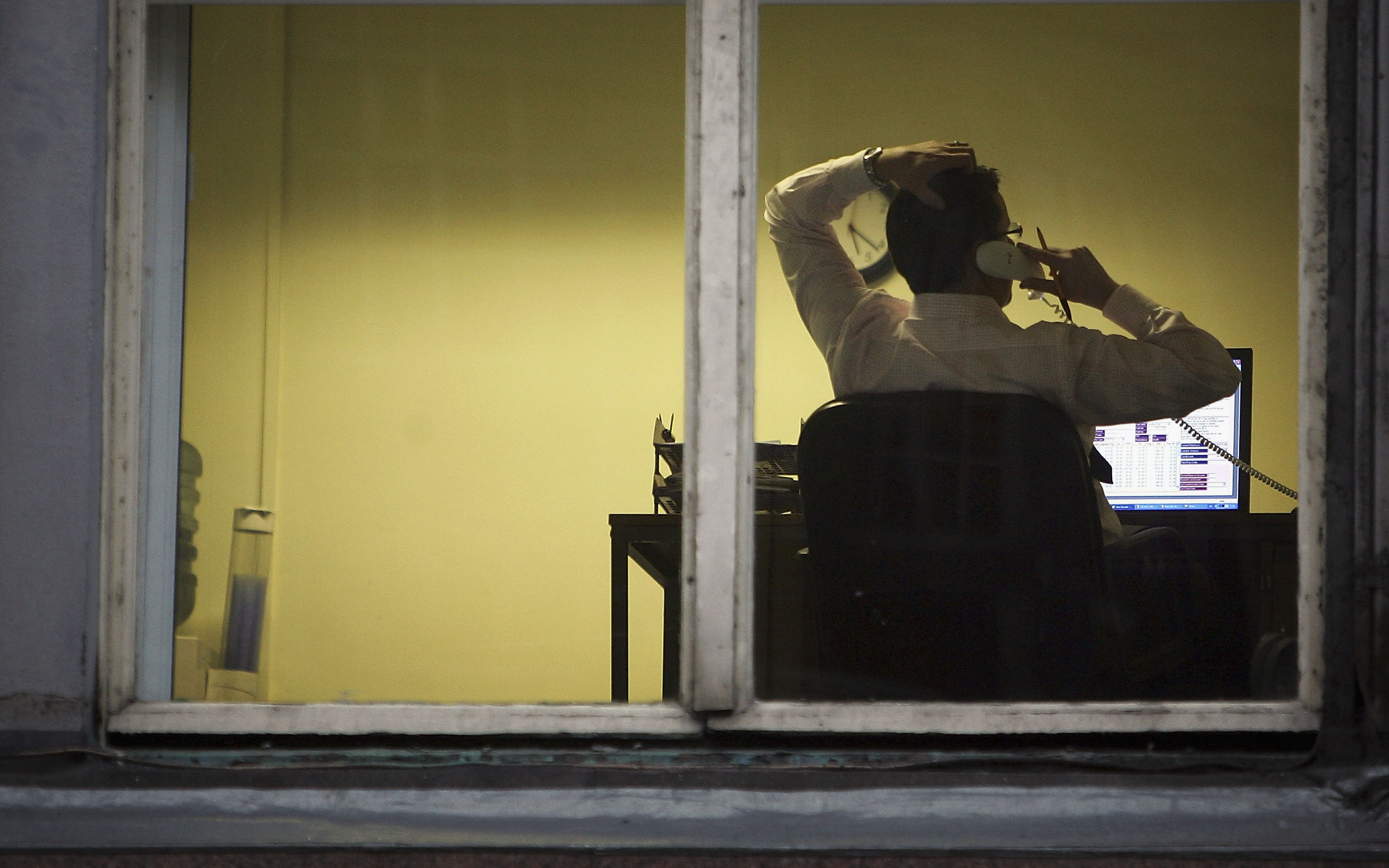 A city office employee works into the night as darkness closes in on October 10, 2005 in Glasgow, Scotland.