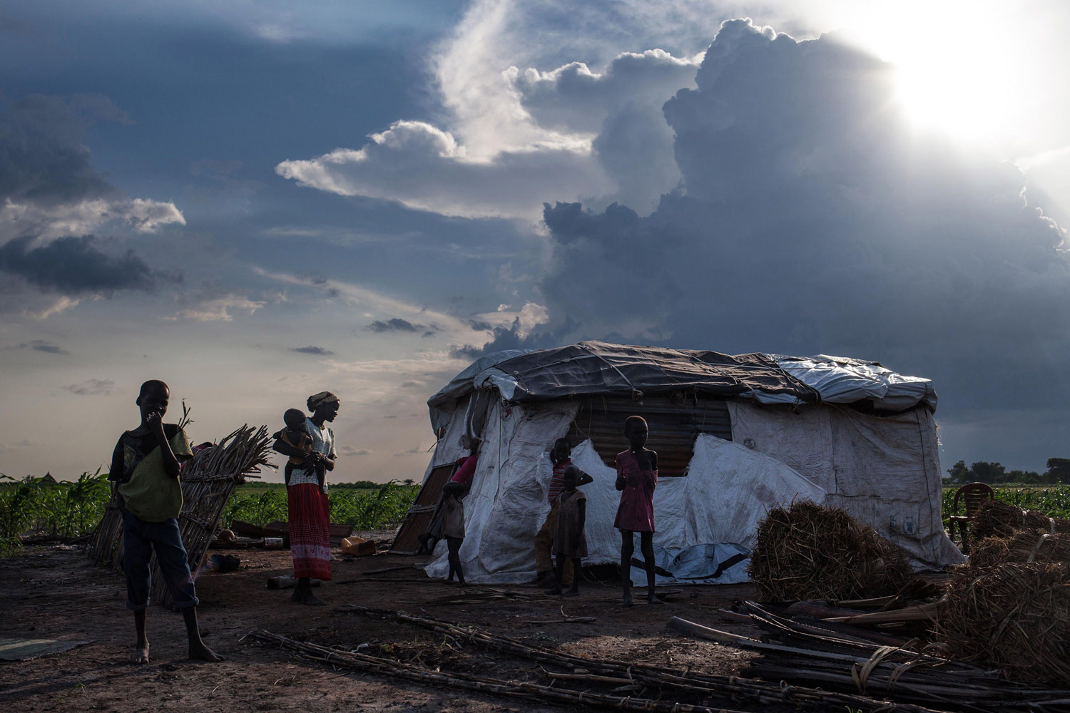 Jul. 5, 2014. Martha Nyarueni (2ndL) and her family stand outside their home outside the town of Leer, South Sudan, after receiving an aid package.