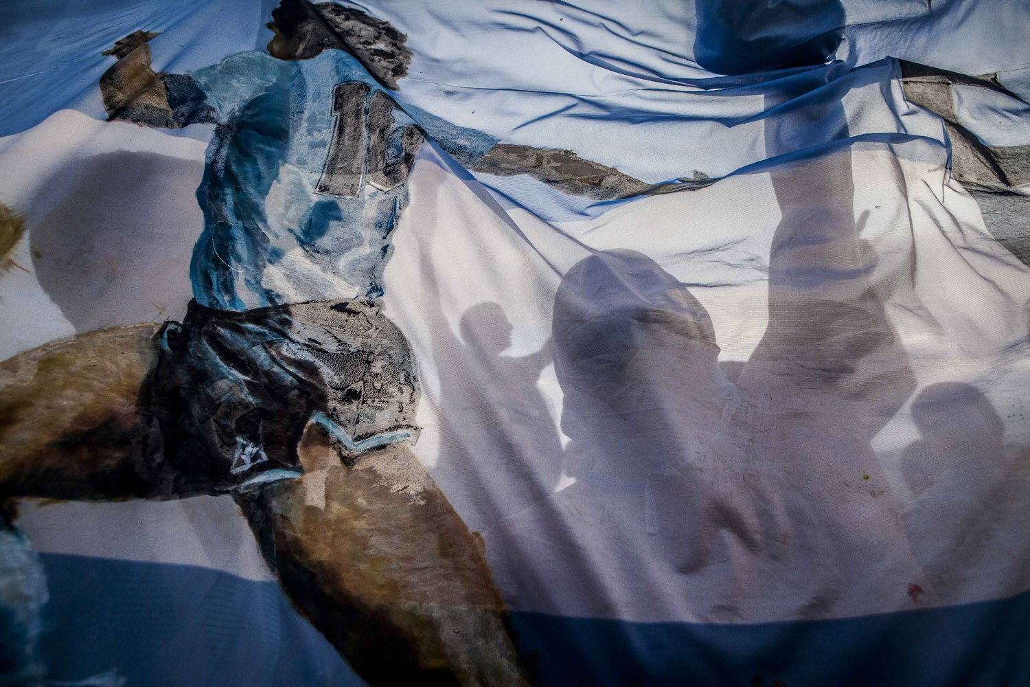 Jul. 9, 2014. Argentina supporters seen behind a flag with the figure of Maradona before the semi-final match against Holland at the Fan Fest in Copacabana Beach.