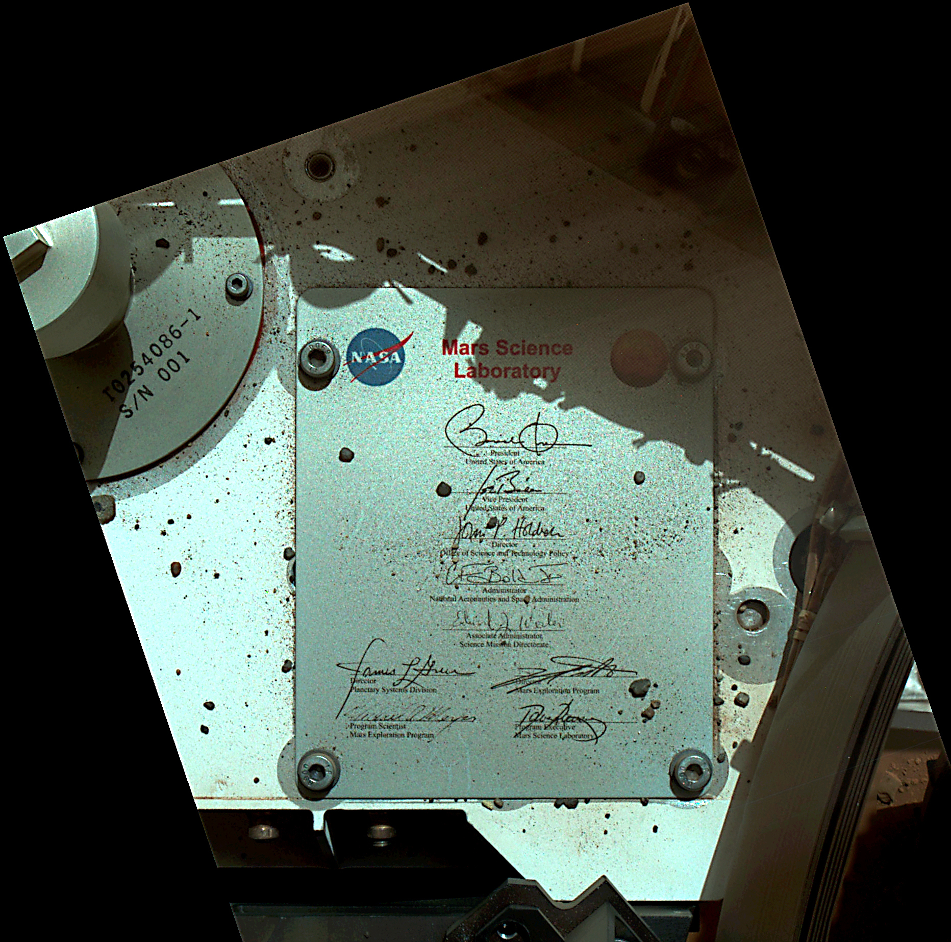 This view of Curiosity's deck shows a plaque bearing several signatures of US officials, including that of President Obama and Vice President Biden. The image was taken by the rover's Mars Hand Lens Imager (MAHLI) during the rover's 44th Martian day, or sol, on Mars (Sept. 19, 2012). The plaque is located on the front left side of the rover's deck.