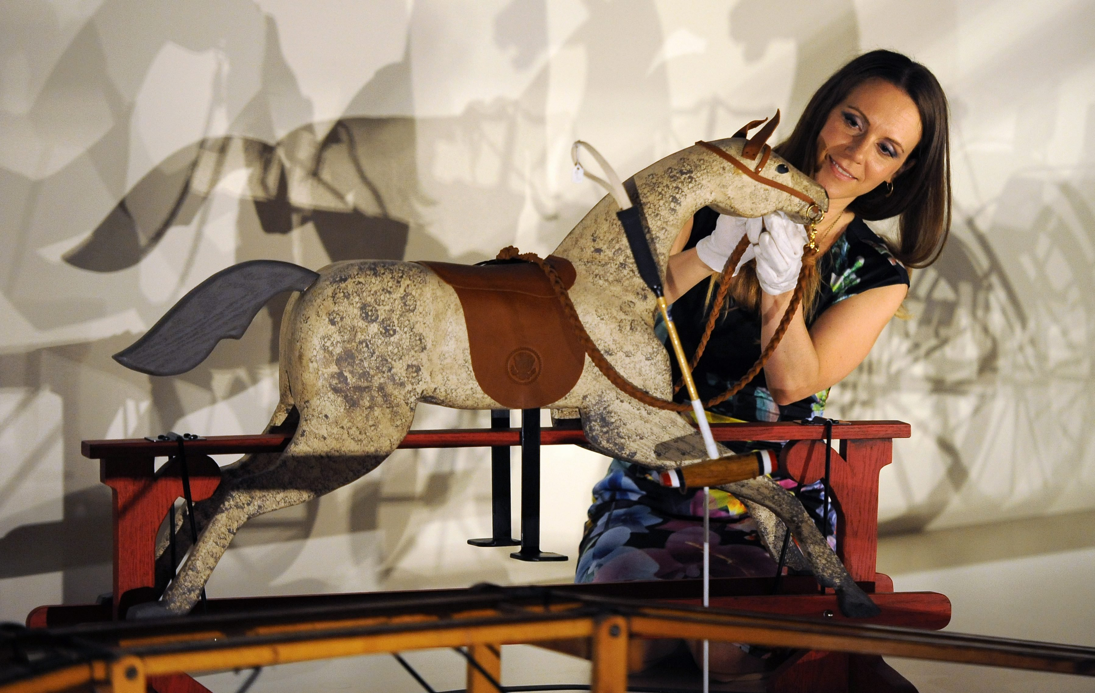 Curator Anna Reynolds adds the finishing touches to a rocking horse presented to Prince George of Cambridge by U..S President Barak Obama and his wife Michelle Obama at the 'Royal Childhood' exhibition at Buckingham Palace in London on July 24, 2014.