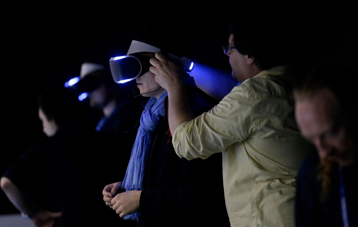 Two men get help putting on the PlayStation 4 virtual reality headset Project Morpheus in a demo area at the Game Developers Conference 2014 in San Francisco on March 19, 2014.