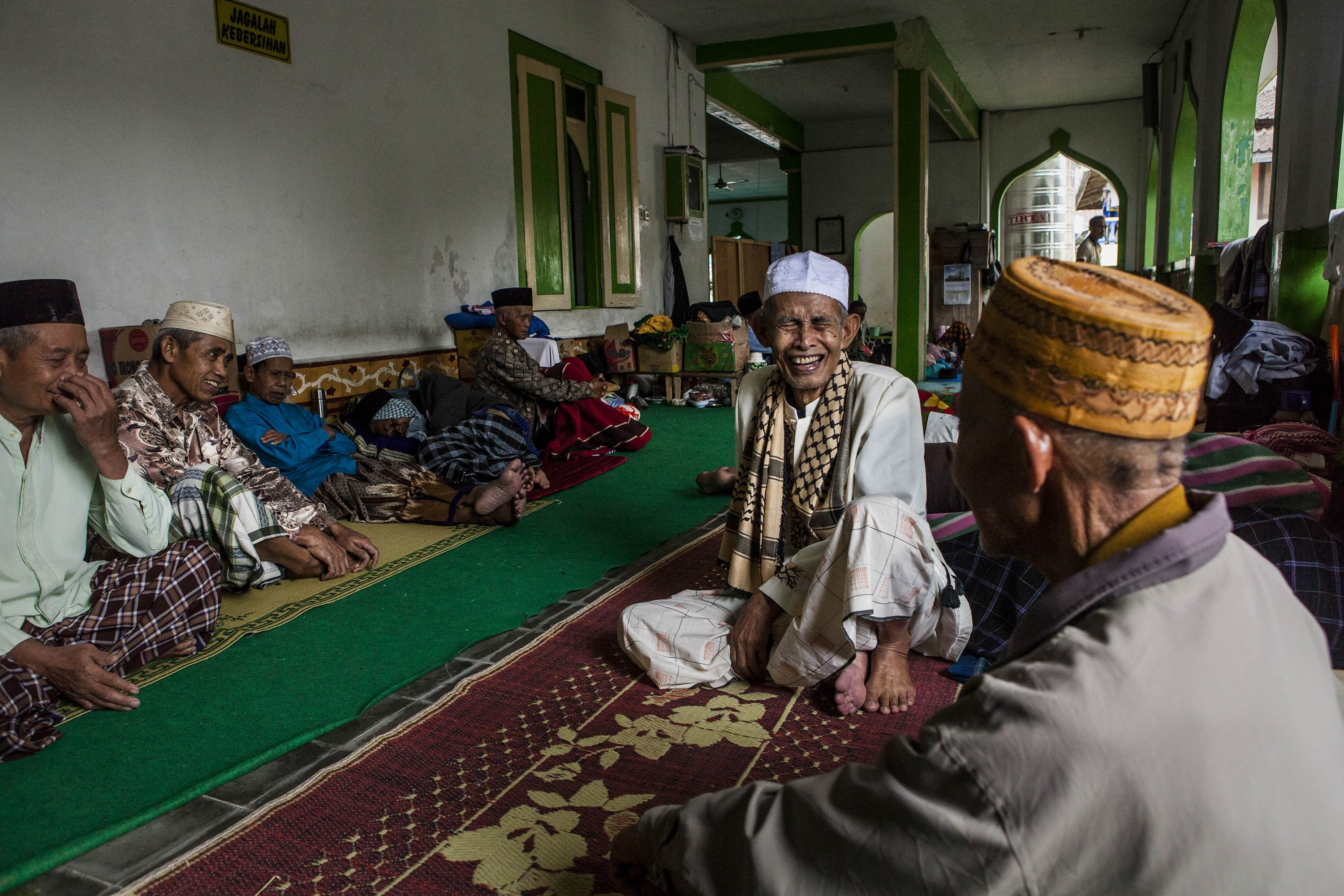 Elderly men talk to each other as they take a break at a boarding school that cares for the elderly during Ramadan in Central Java, Indonesia on July 15, 2014.