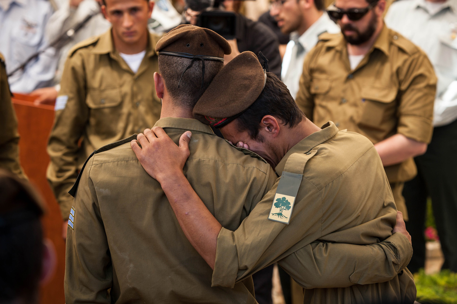 Jul. 23, 2014. Comrades of slain Sgt. Max Steinberg comfort each other during his                               funeral.