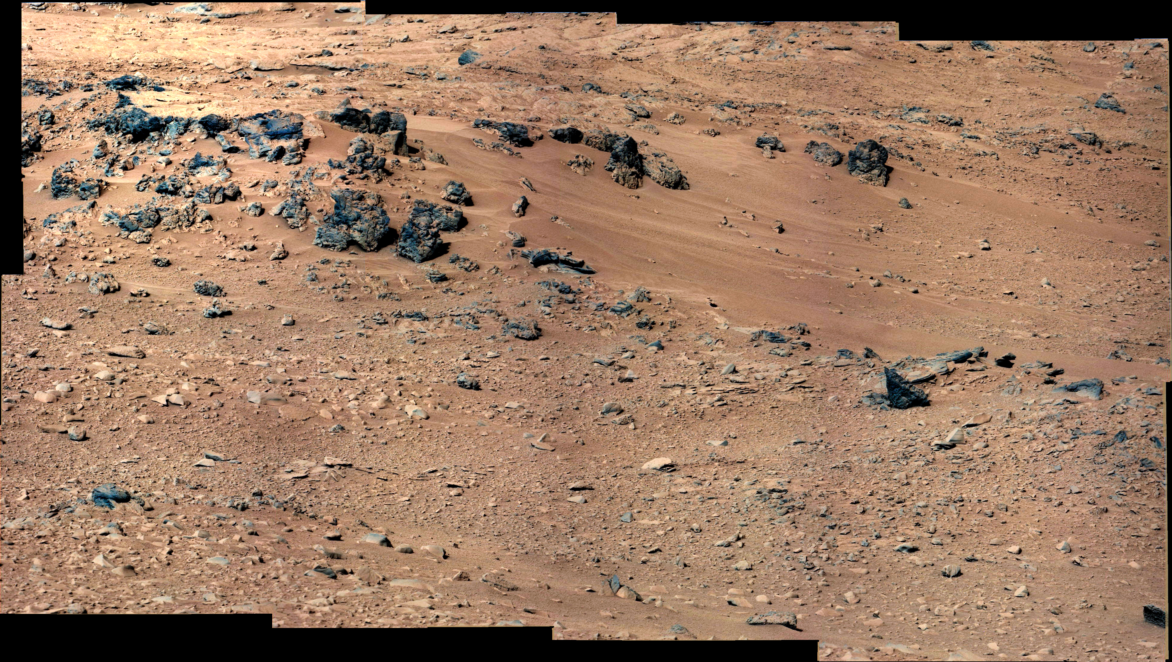 This patch of windblown sand and dust downhill from a cluster of dark rocks is the  Rocknest  site, which has been selected as the likely location for first use of the scoop on the arm of NASA's Mars rover Curiosity. This view is a mosaic of images taken by the telephoto right-eye camera of the Mast Camera (Mastcam) during the 52nd Martian day, or sol, of the mission (Sept. 28, 2012).