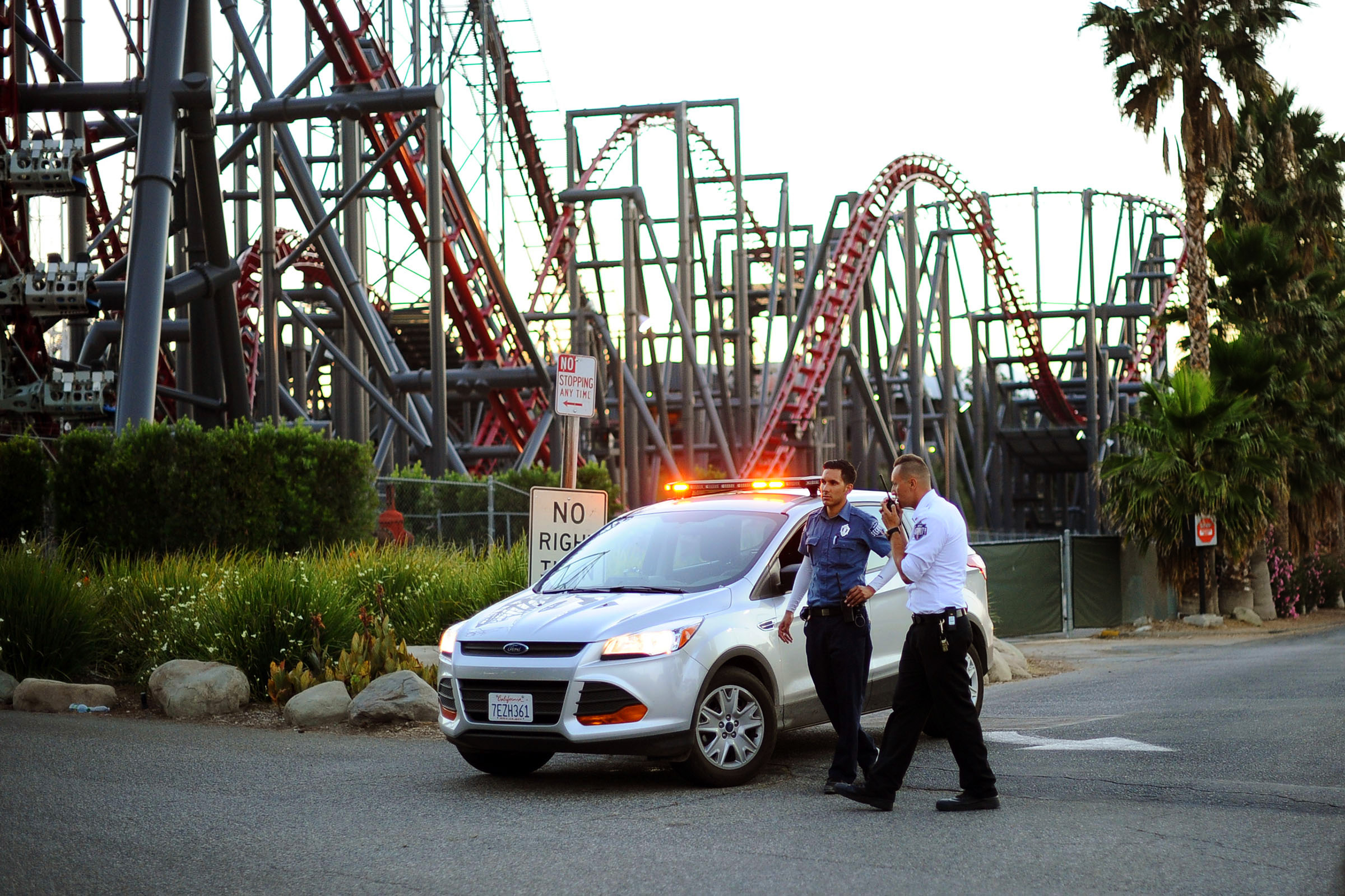 Members of the Six Flags Magic Mountain amusement park security staff monitor the situation at the exit of the park after riders were injured on the Ninja coaster