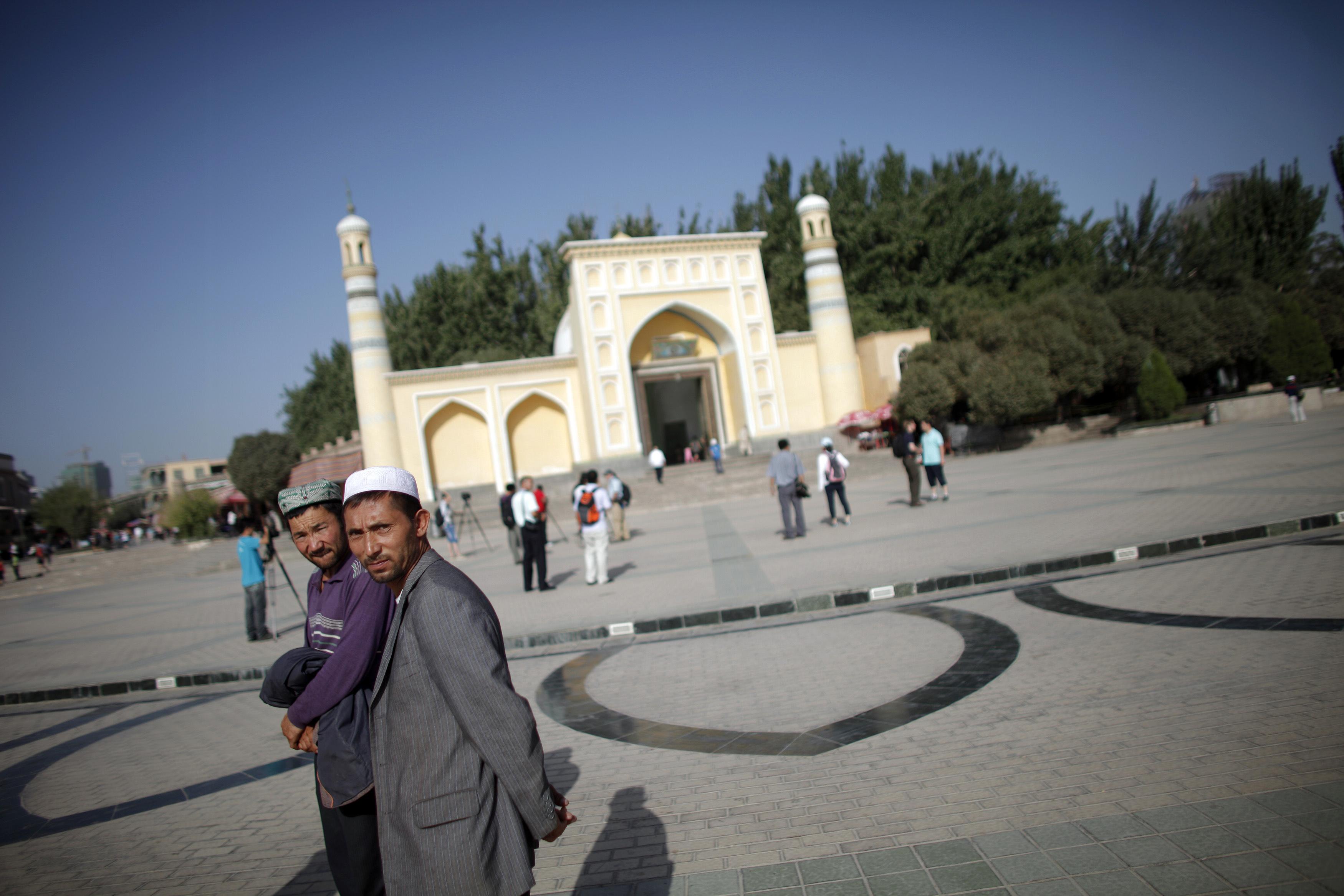 Ethnic Uighur men walk outside a mosque in Kashgar, Xinjiang province, on Aug. 3, 2011.