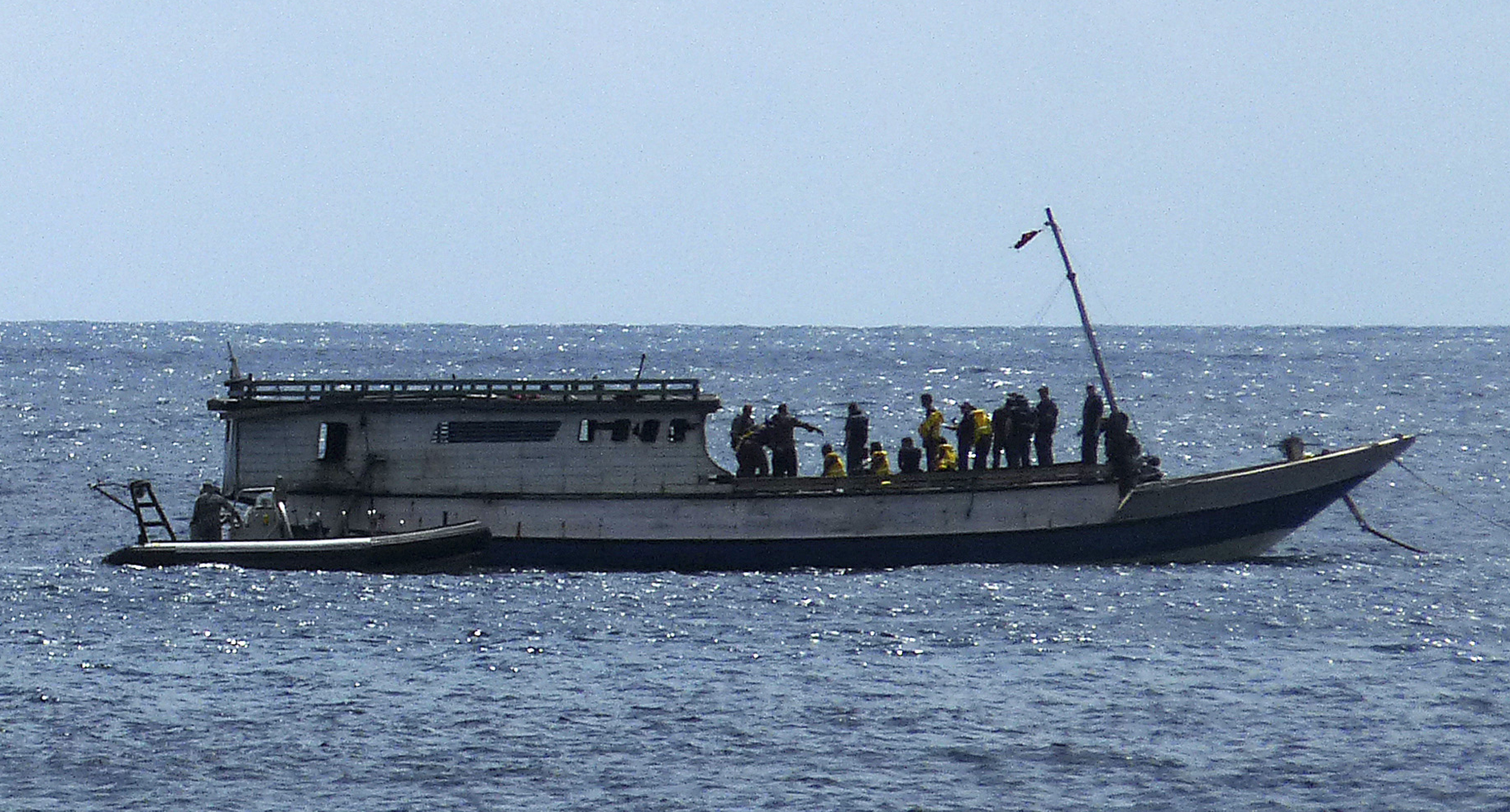 An Australian navy boat, front left, comes alongside a boat carrying 50 asylum seekers after it arrived at Flying Fish Cove on Christmas Island, about 2,600 km (1,600 miles) northwest of Perth, on Aug. 7, 2011.