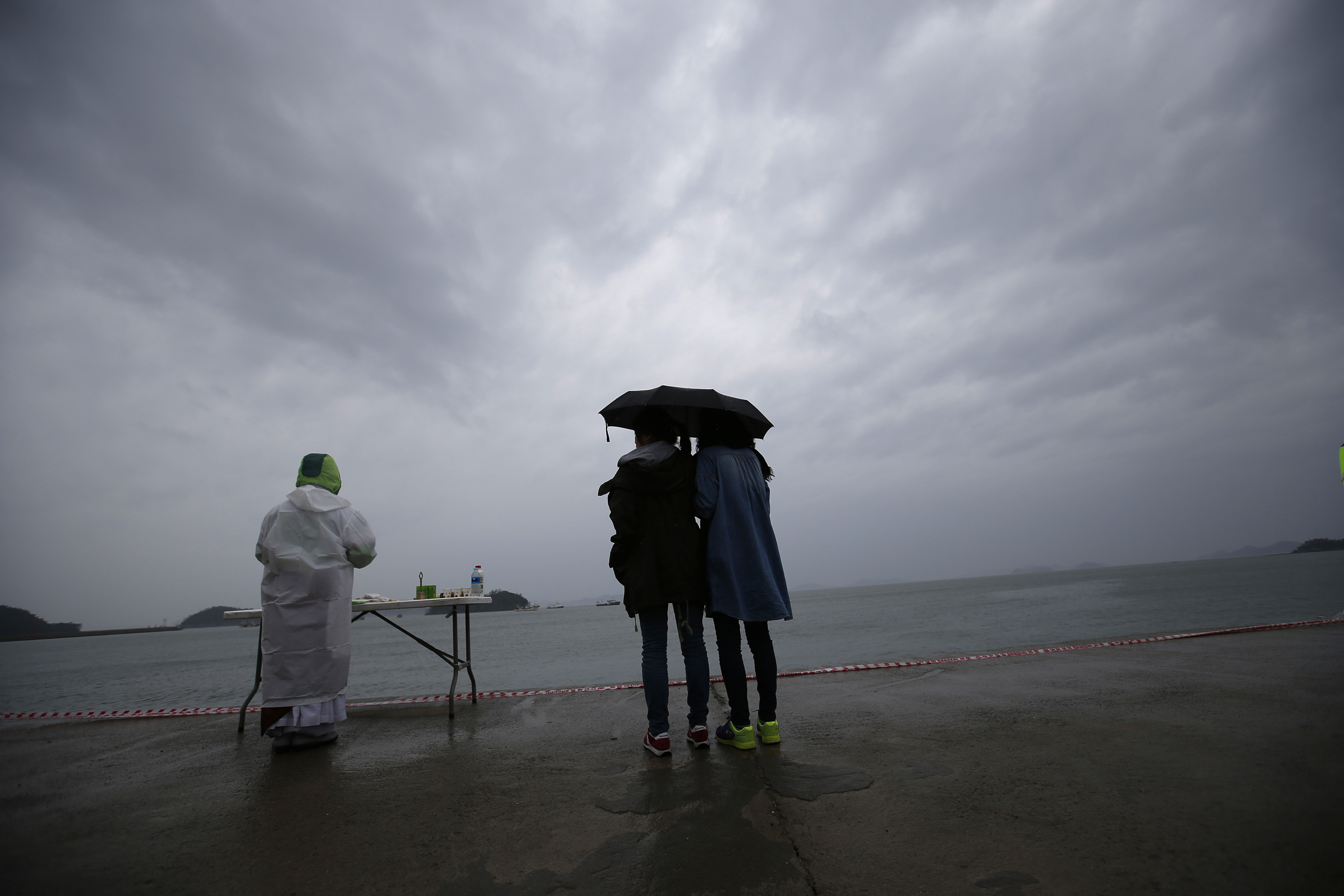 Relatives of a missing passenger onboard the capsized Sewol ferry look at the sea while a Buddhist monk prays for the victims at a port in the rain, where family members wait for news from the search and rescue team on April 27, 2014.