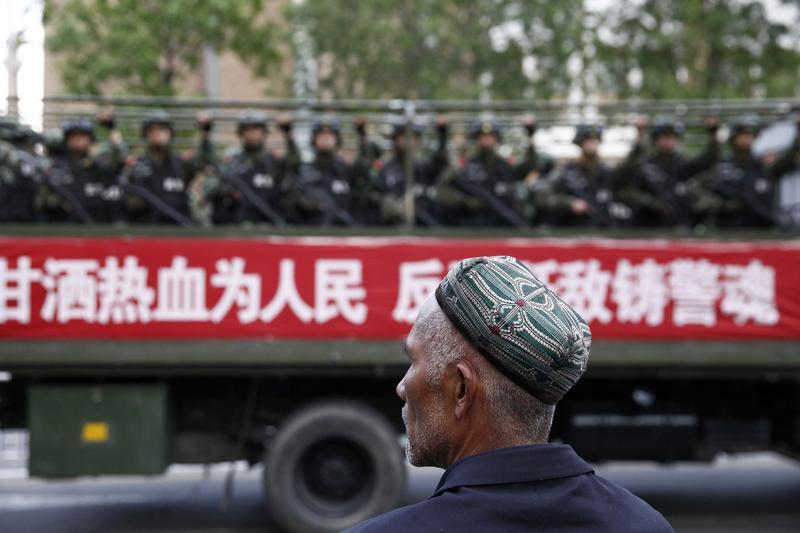 A Uighur man looks on as a truck carrying paramilitary policemen travel along a street during an antiterrorism oath-taking rally in Urumqi, China's Xinjiang region, on May 23, 2014