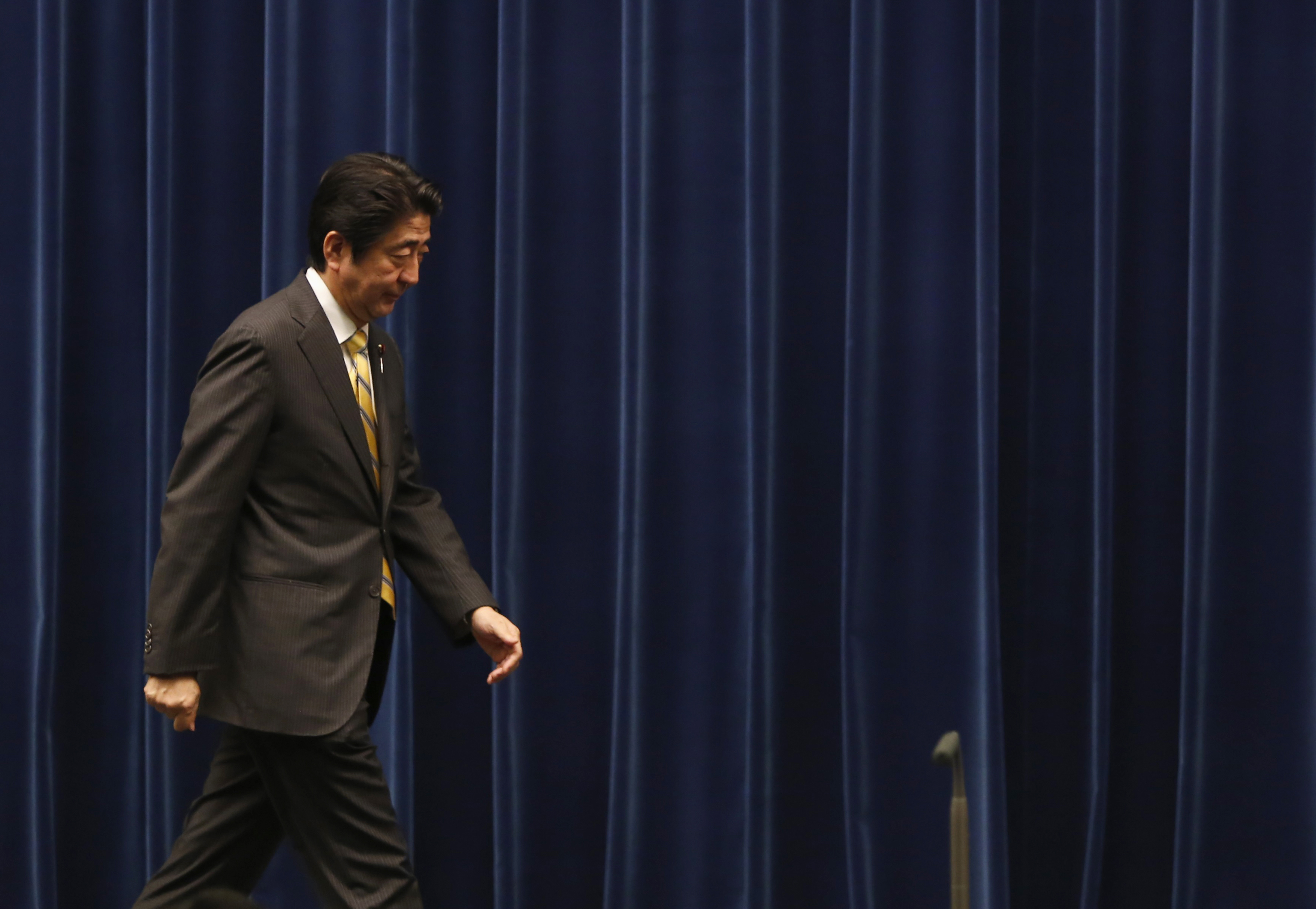 Japan's Prime Minister Shinzo Abe leaves a news conference at his official residence in Tokyo on June 24, 2014.  Abe has unveiled a package of measures aimed to boost Japan's long-term economic growth, from phased-in corporate tax cuts to a bigger role for women and foreign workers