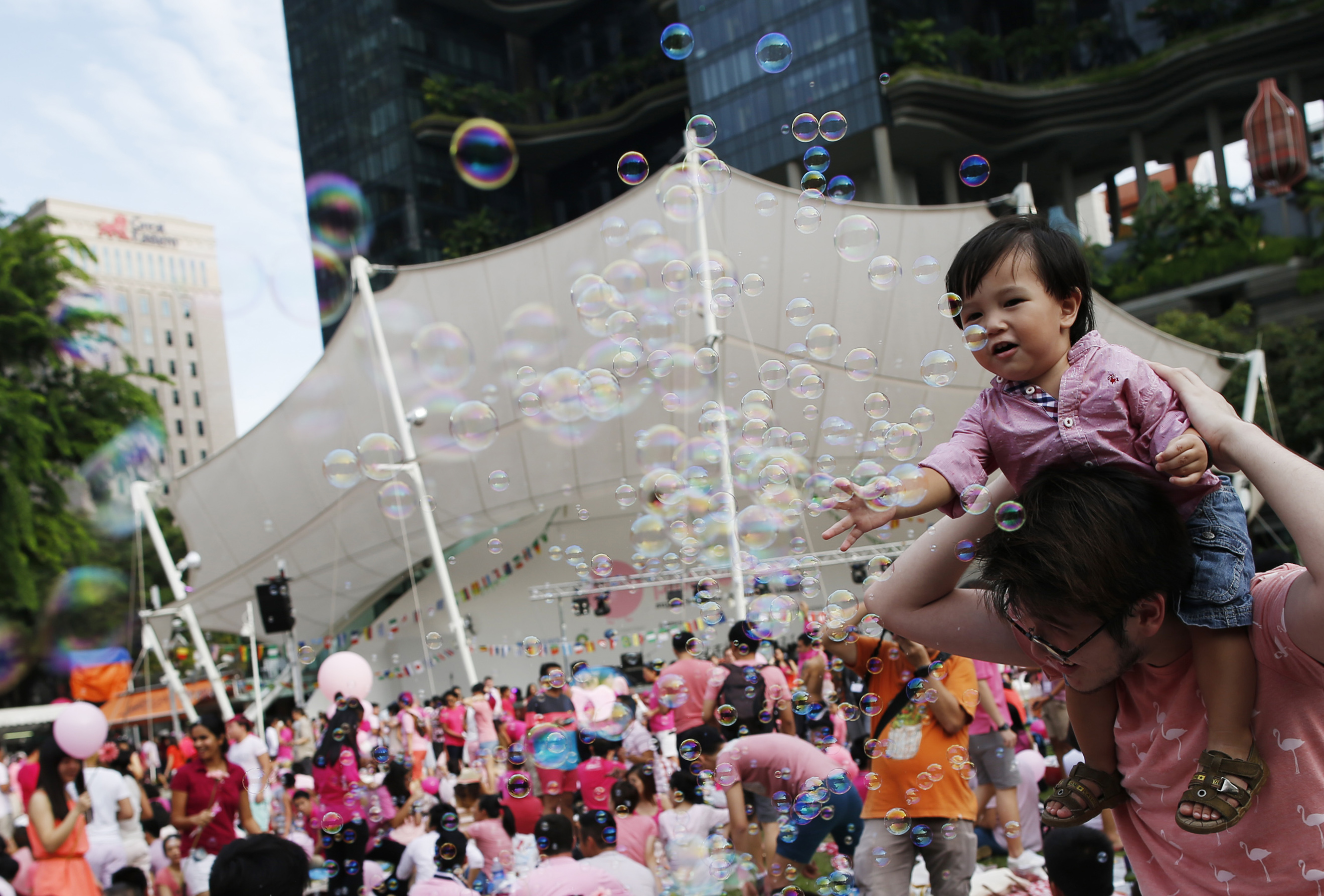 A toddler plays with bubbles during the Pink Dot parade at the Speakers' Corner in Hong Lim Park in Singapore June 28, 2014.