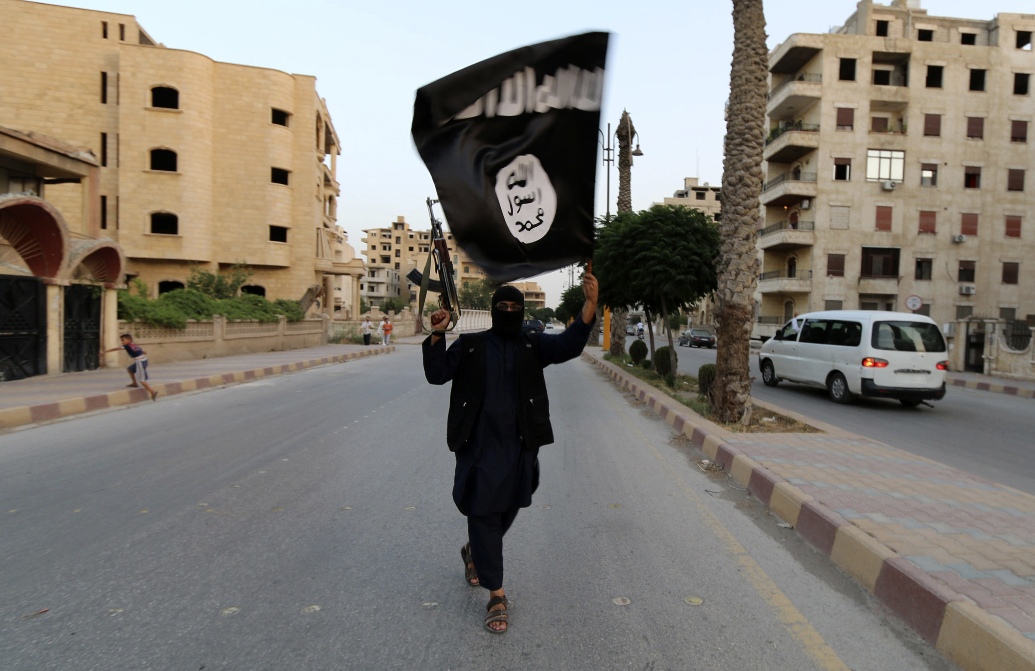 A member loyal to the Islamic State in Iraq and the Syria waves an ISIS flag in Raqqa, Syria on June 29, 2014.