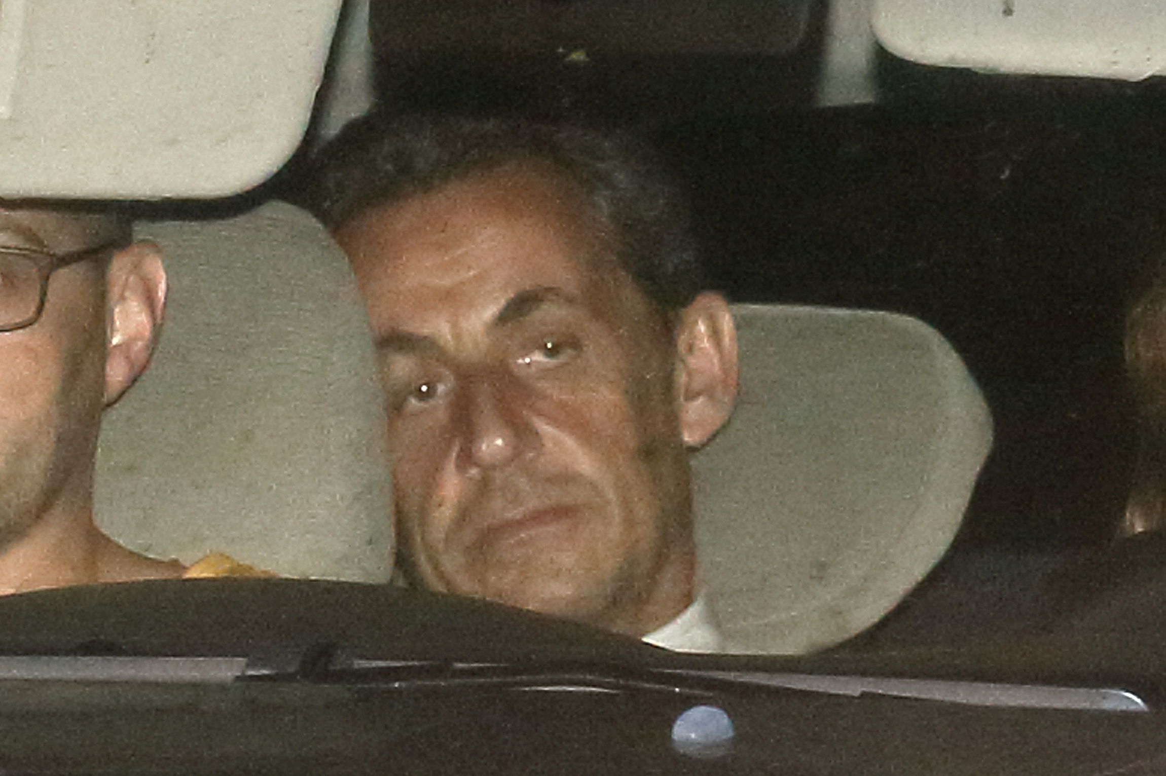 Former French President Nicolas Sarkozy arrives with police by car at the financial investigation unit in Paris to be presented to a judge late July 1, 2014. Former French President Sarkozy was held for questioning for 15 hours on Tuesday over suspicions he used his influence to secure leaked details of an inquiry into alleged irregularities in his 2007 election campaign.