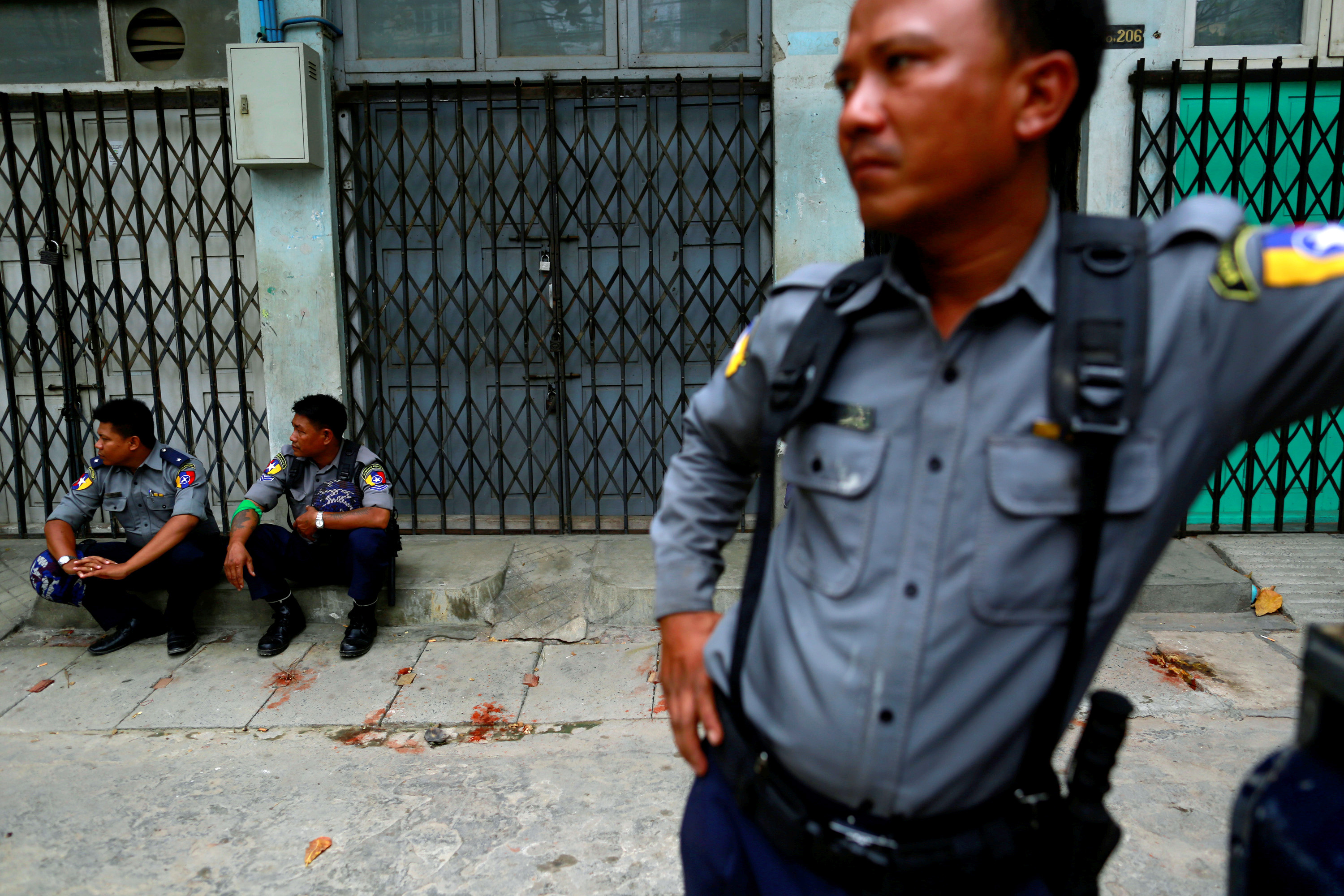 Police officers guard a Muslim residential area in Mandalay July 3, 2014.