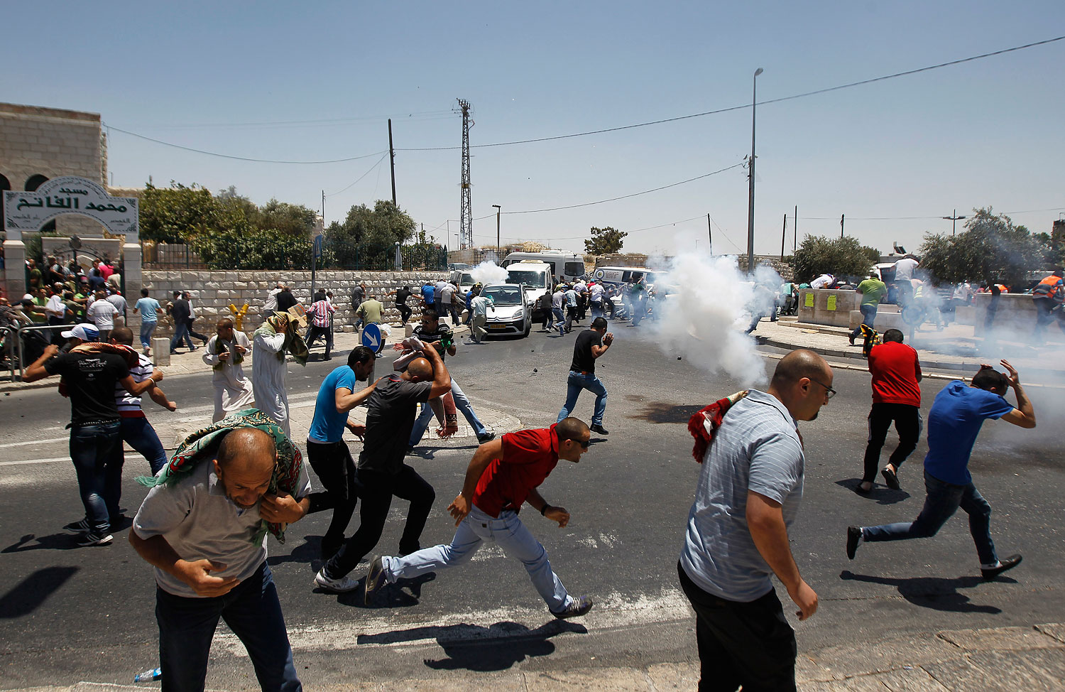 Palestinian protesters run away from tear gas fired by Israeli soldiers during clashes after Friday prayers in the Arab east Jerusalem neighbourhood of Ras al-Amud, July 4, 2014.