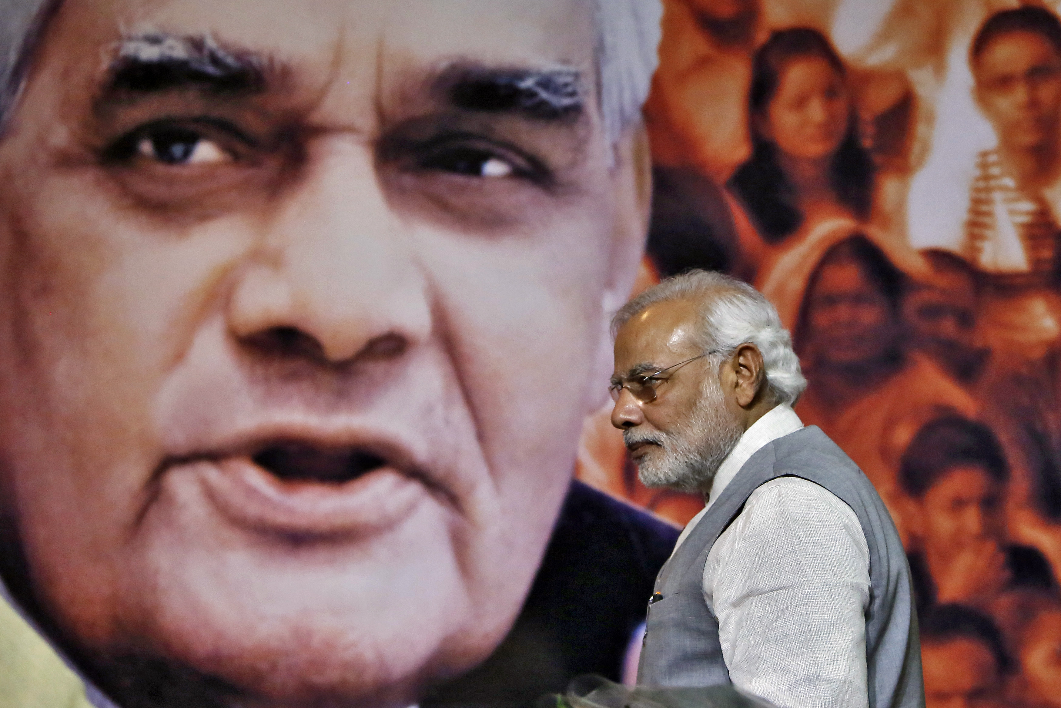 Indian Prime Minister Narendra Modi walks in front of a picture of former Indian Prime Minister Atal Bihari Vajpayee after a news conference in New Delhi on July 9, 2014.