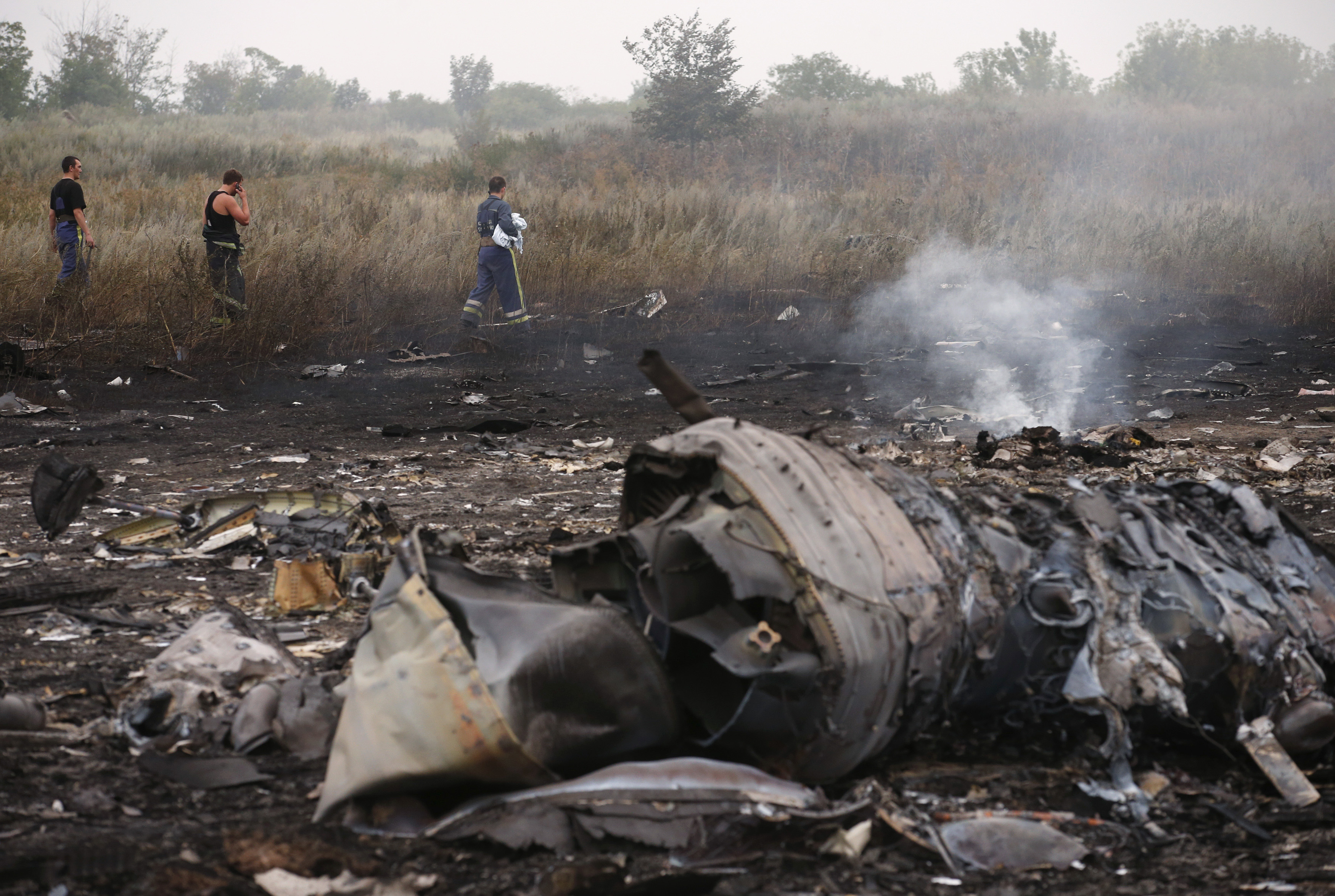Emergencies Ministry members walk at the site of a Malaysia Airlines Boeing 777 plane crash, MH17, near the settlement of Grabovo in the Donetsk region, on July 17, 2014.