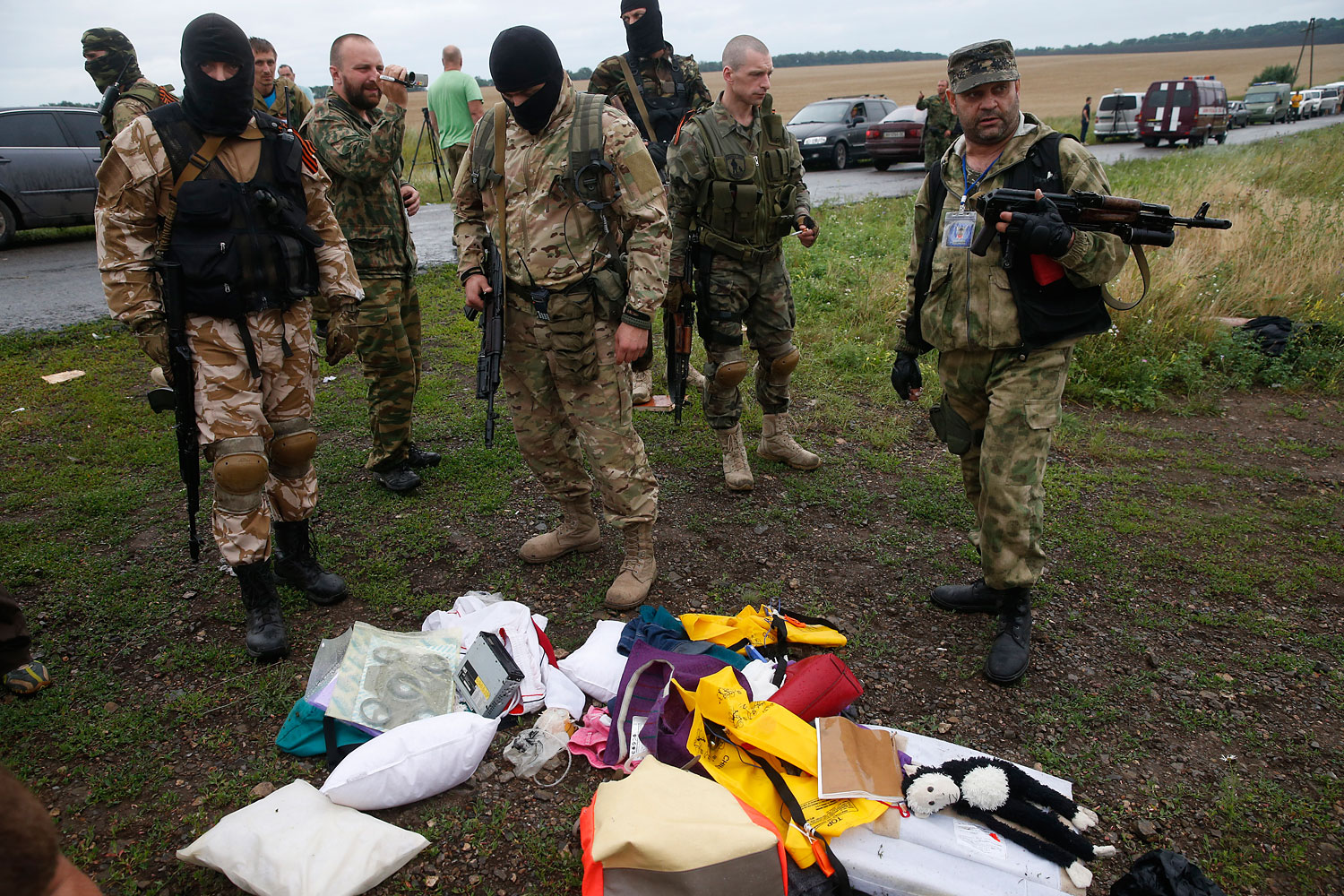 Pro-Russian separatists look at passengers' belongings at the crash site of Malaysia Airlines flight MH17, near the settlement of Grabovo in the Donetsk region, July 18, 2014.