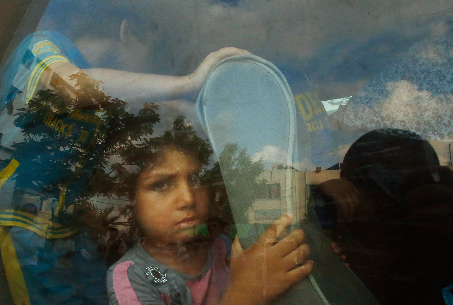 A Palestinian girl sits in a minibus after fleeing her family's house during heavy Israeli shelling, in Gaza City July 20, 2014.