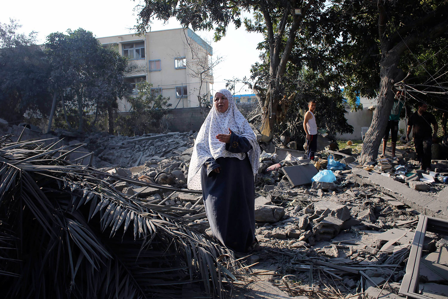 A Palestinian woman gestures as she stands amidst the rubble of her house which police said was destroyed in an Israeli air strike in Rafah in the southern Gaza Strip, July 20, 2014.