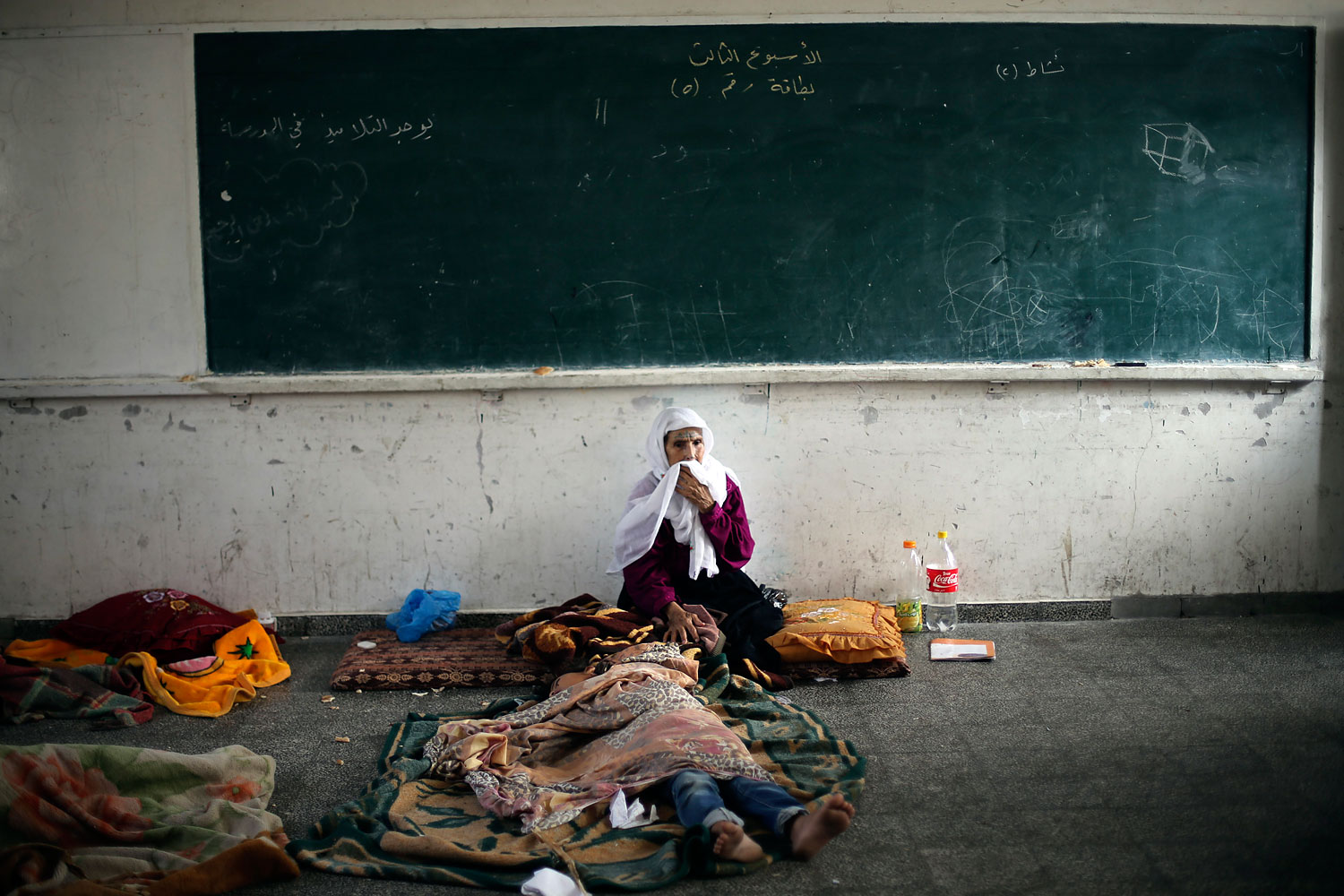 A Palestinian woman, who fled her house following an Israeli ground offensive, stays at a United Nations-run school in Rafah in the southern Gaza Strip July 20, 2014.