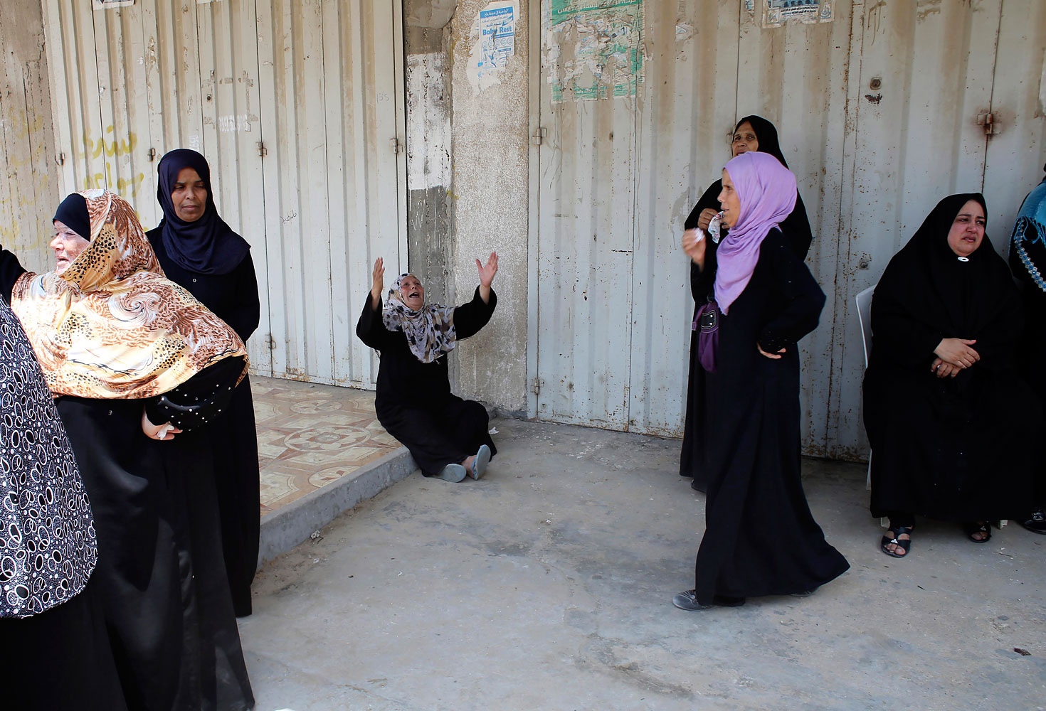 Relatives of three Palestinians from Abu Muamar family, who medics said were killed in an Israeli air strike, mourn during their funeral in Rafah in the southern Gaza Strip July 20, 2014.