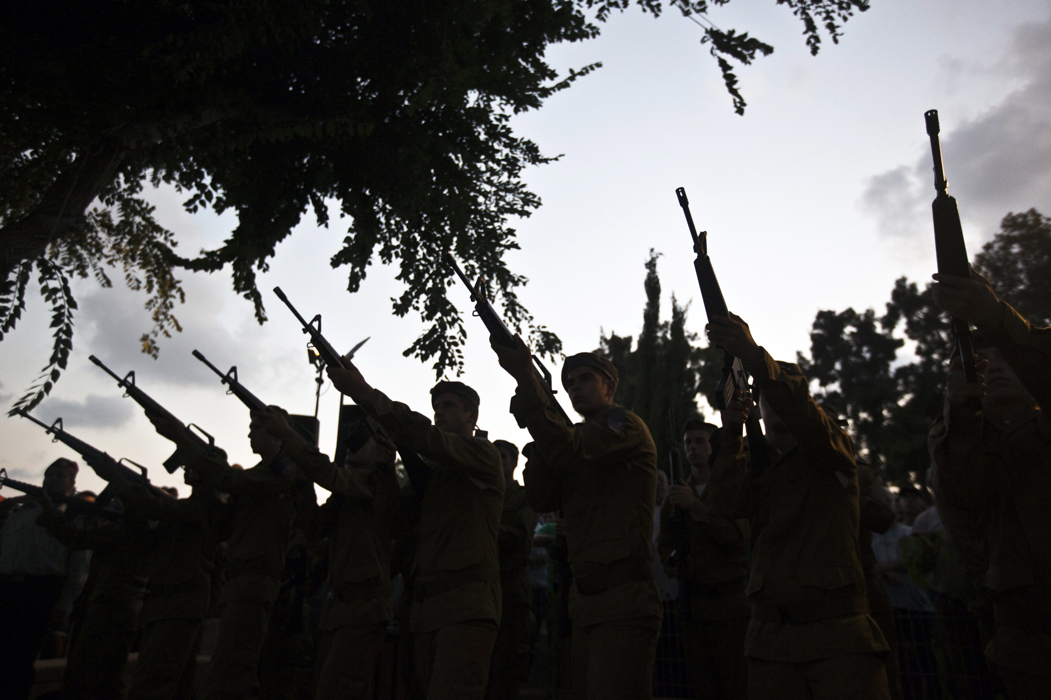 Israeli soldiers fire their weapons during the funeral of their comrade Bnaya Rubel in Holon, near Tel Aviv July 20, 2014.
