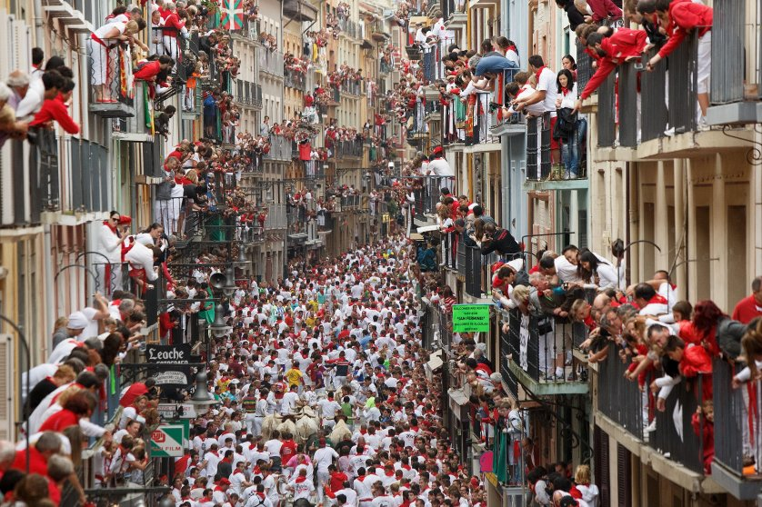 Revellers run with Torrestrella's fighting bulls along the Calle Estafeta during the second day of the San Fermin Running Of The Bulls festival on July 7, 2014 in Pamplona, Spain.