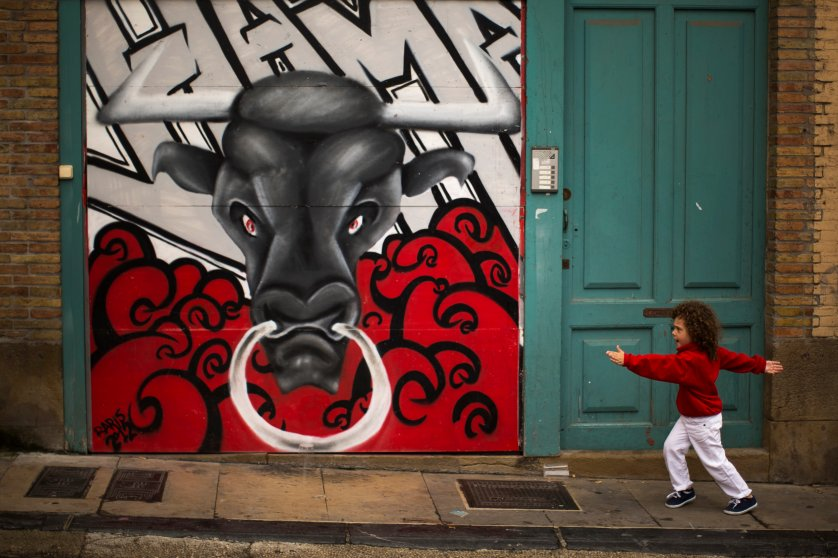 A young reveler dressed in a traditional outfit runs next to a mural of a bull during the opening day of the 2014 San Fermin fiestas in Pamplona, Spain on July 6, 2014.