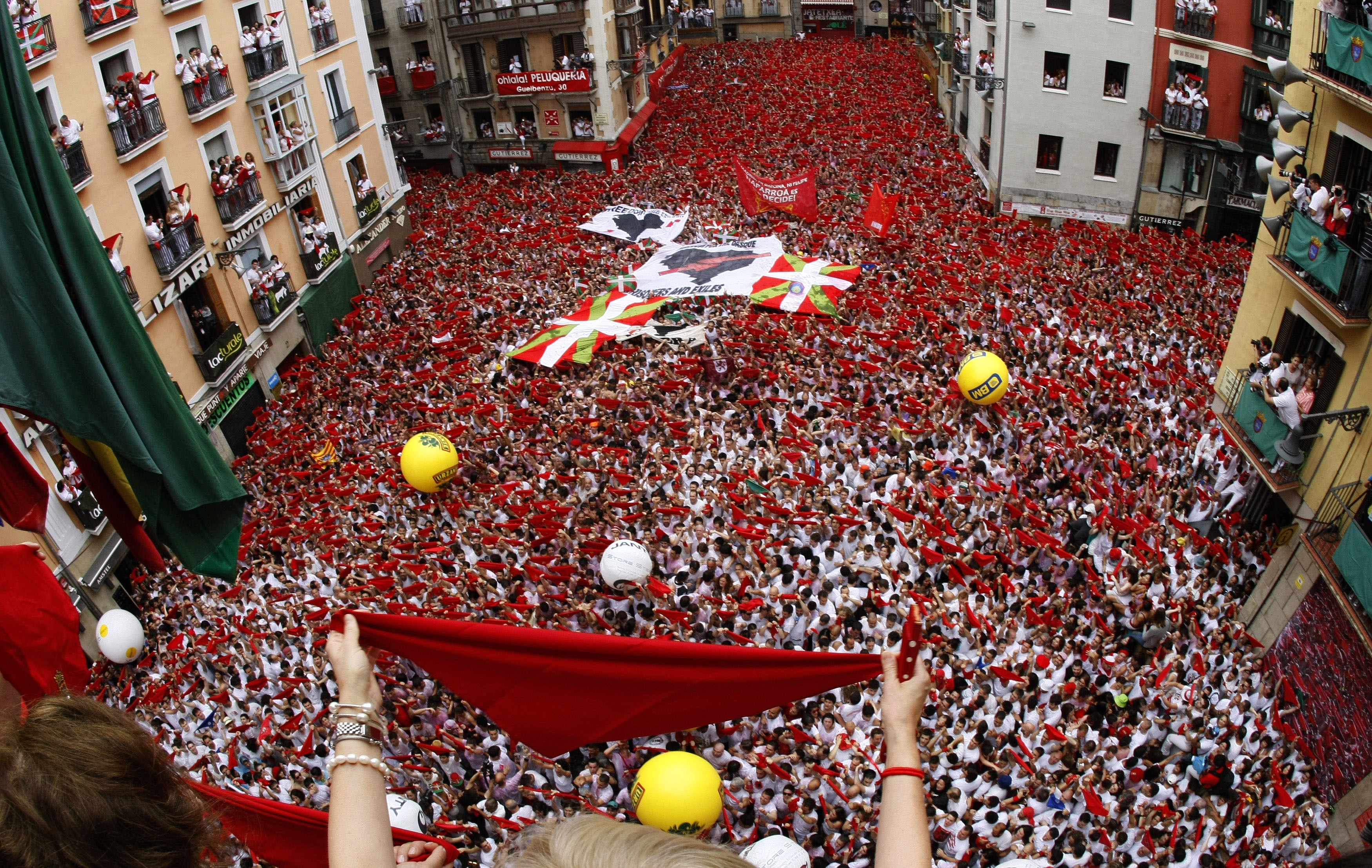 People cheer after hearing the midday Chupinazo rocket announcing the start of the San Fermin festival in Pamplona on July 6, 2014.