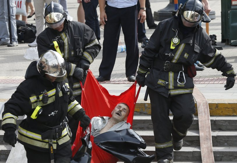 Rescuers carry a passenger injured as several subway cars derailed in Moscow, on July 15, 2014.
