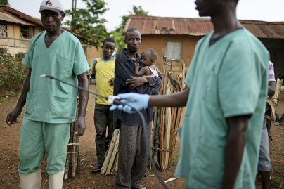Locals watch workers with Doctors Without Borders as they disinfect after leaving a private clinic, where they've been working to combat the spread of the Ebola virus, Teldou, Guinea, July 10, 2014.