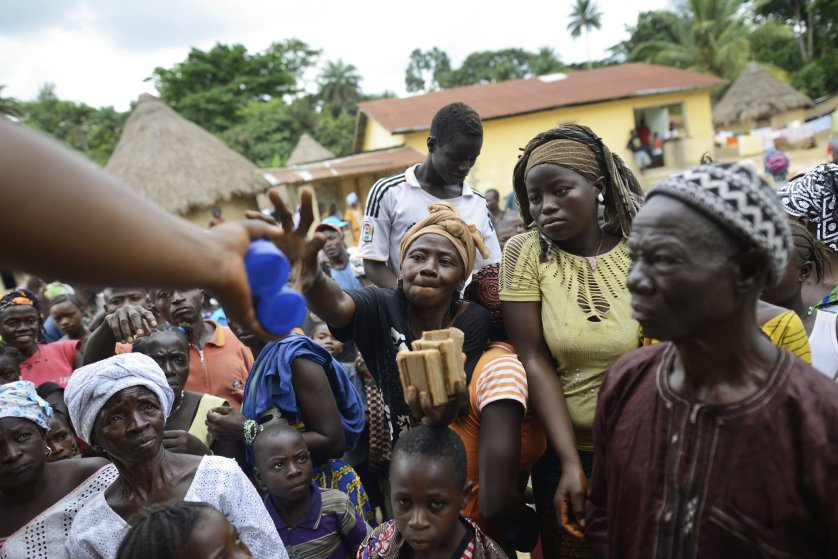 Members of the World Health Organization and Red Cross hand out chlorine and medical soap to combat the spread of the Ebola virus in Bawa, Guinea.