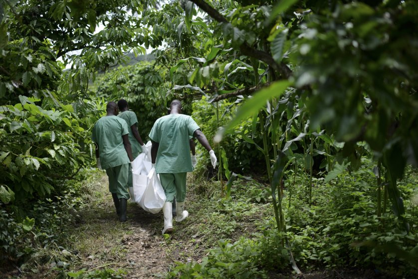 Red Cross workers carry the body of Marie Conde, 14, who died of Ebola, through the bush in Koundony, Guinea.
