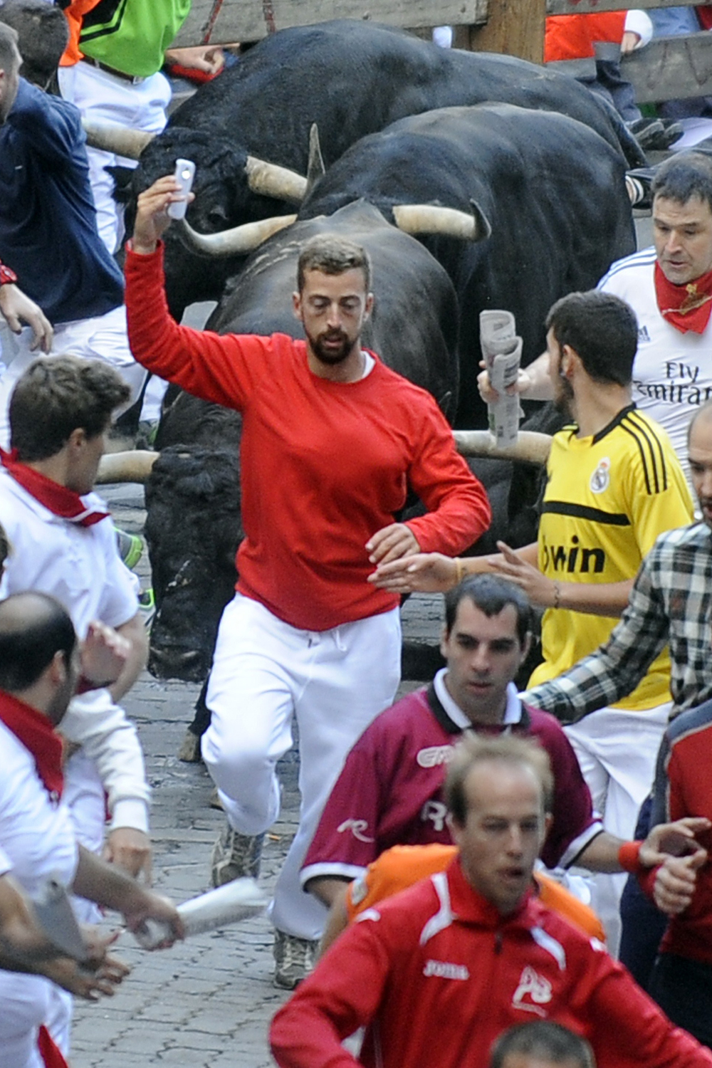 A participant runs in front of Jandilla's bulls as he takes a 'selfie' (photograph of himself) during the fifth bull-run of the San Fermin Festival in Pamplona, northern Spain, on July 11, 2014.