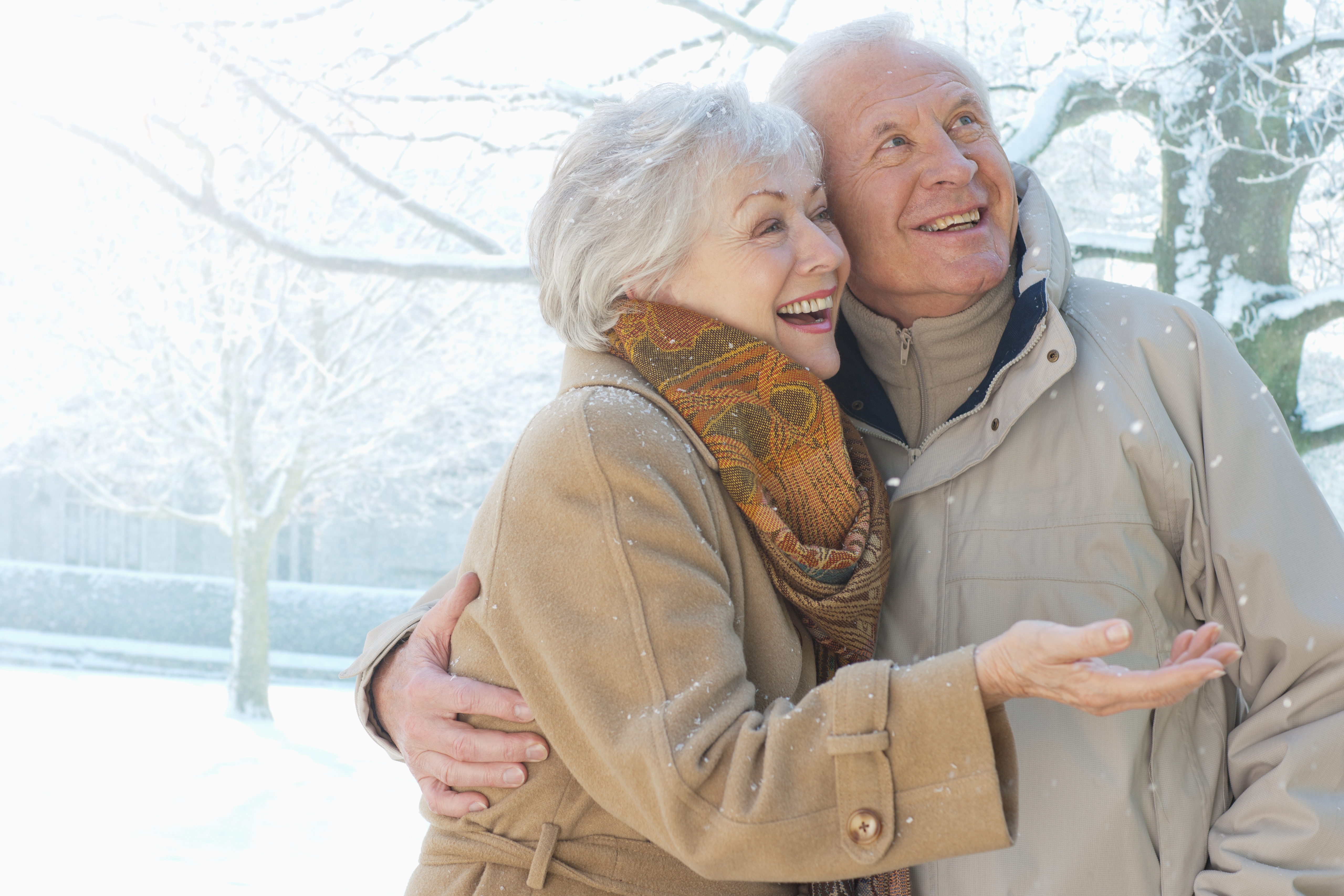 An elderly couple is shown smiling in the snow.