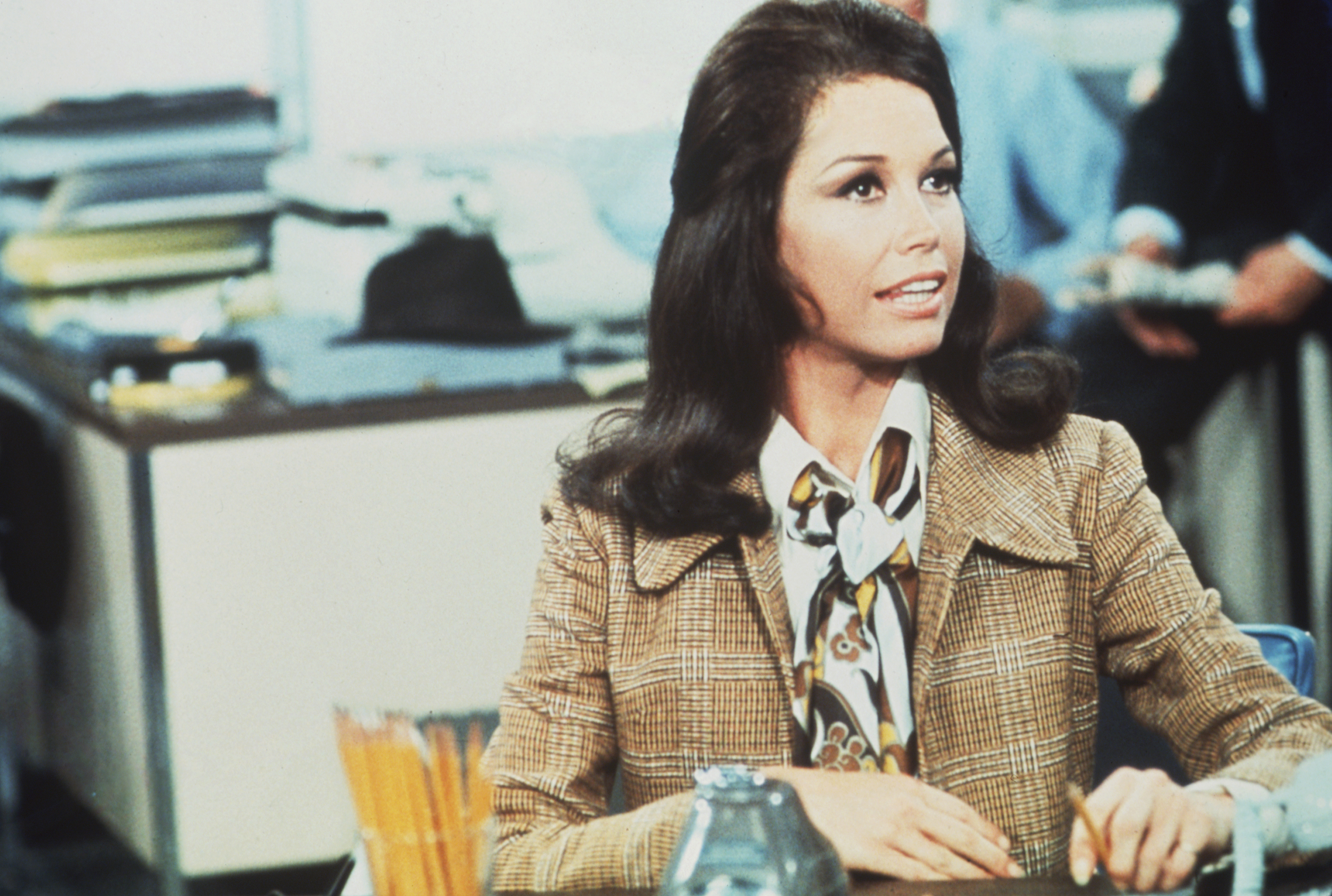 Mary Tyler Moore (as Mary Richards) sits at a desk in a scene from  The Mary Tyler Moore Show.