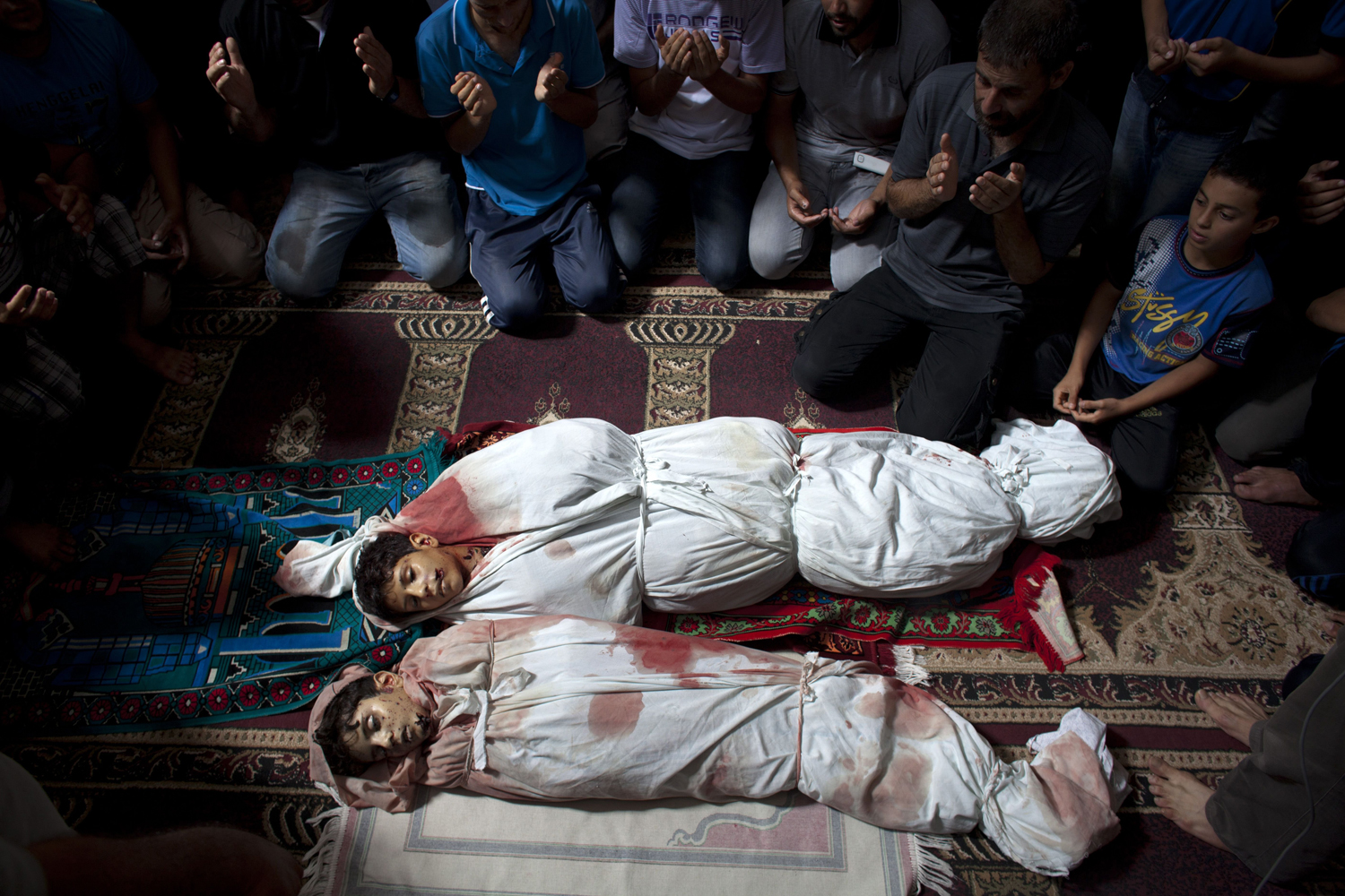 Jul. 9, 2014. Family members pray in the mosque in Sajeria, Gaza, by the bodies of Amir and Mohammed during their funeral.