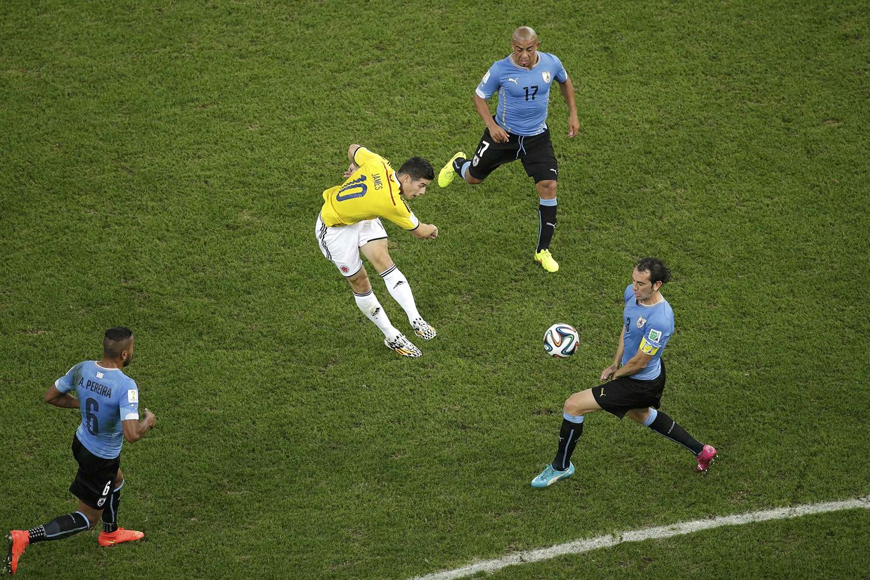 June 28, 2014. Colombia's James Rodriguez (C) scores a goal past Uruguay's Diego Godin (R), Alvaro Pereira (L) and Egidio Arevalo Rios during their 2014 World Cup round of 16 game at the Maracana stadium in Rio de Janeiro, Brazil.
