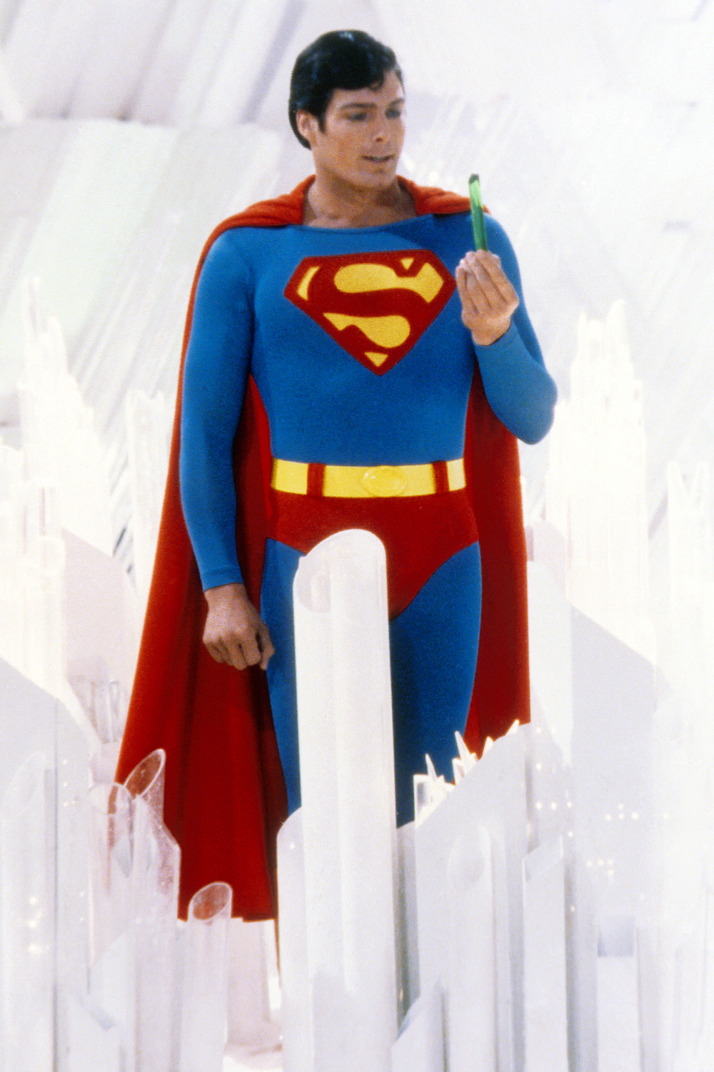 Superman, played by American actor Christopher Reeve (1952 - 2004), holds a green crystal at the Fortress of Solitude, in a promotional still from 'Superman', directed by Richard Donner, 1978.