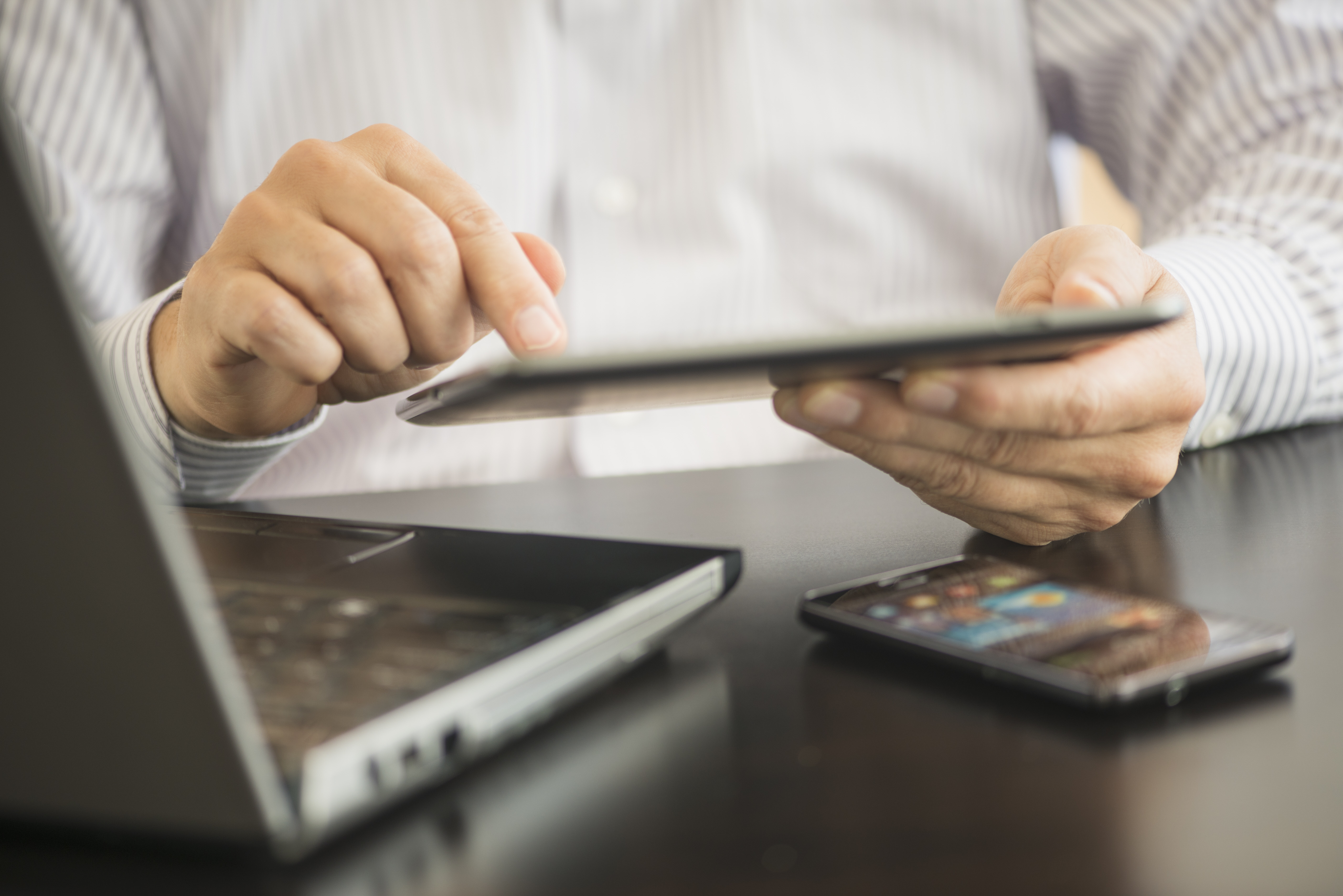 A man uses his tablet PC, laptop and smartphone.