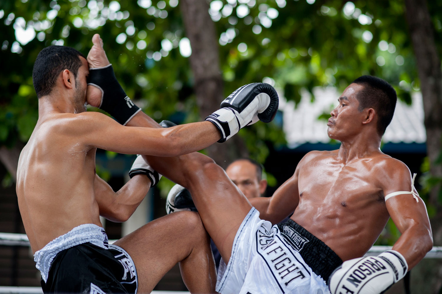 An inmate kicks a foreigner fighter during a Muay Thai fight at Klong Pai prison on July 12, 2014 in Nakhon Ratchasima, Thailand.